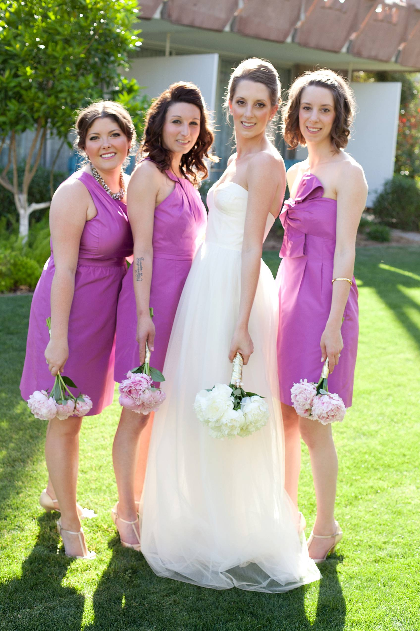 bride in j.crew bridal dress with bridal party walking with sun behind them