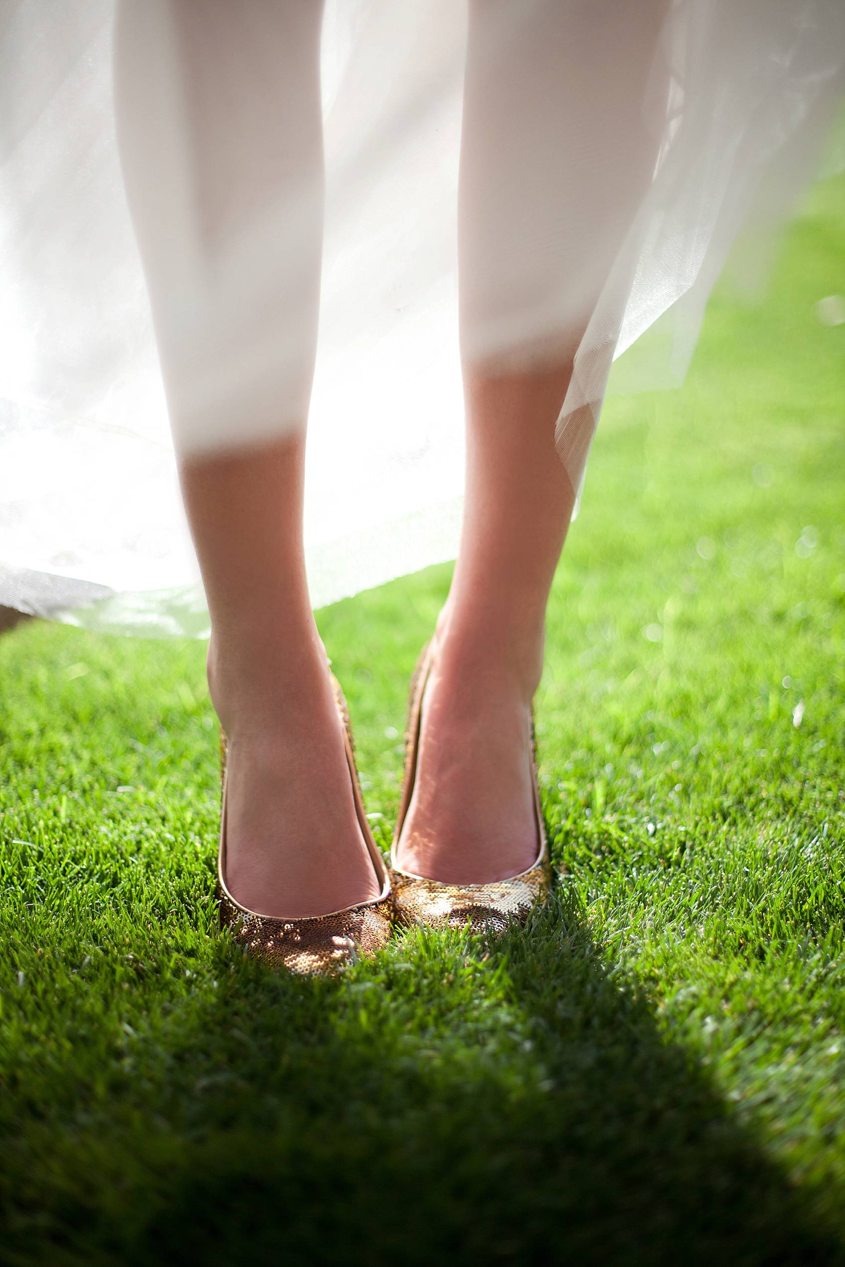 bride in j.crew dress and kate spade gold sparkle shoes with sunlight behind