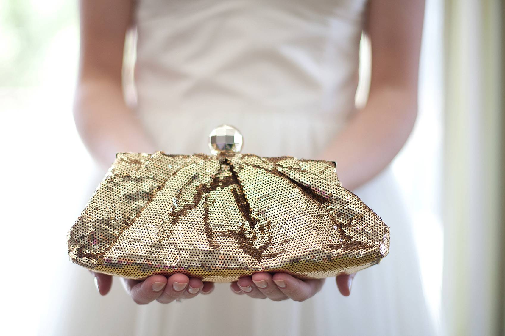bride holding gold sequin clutch