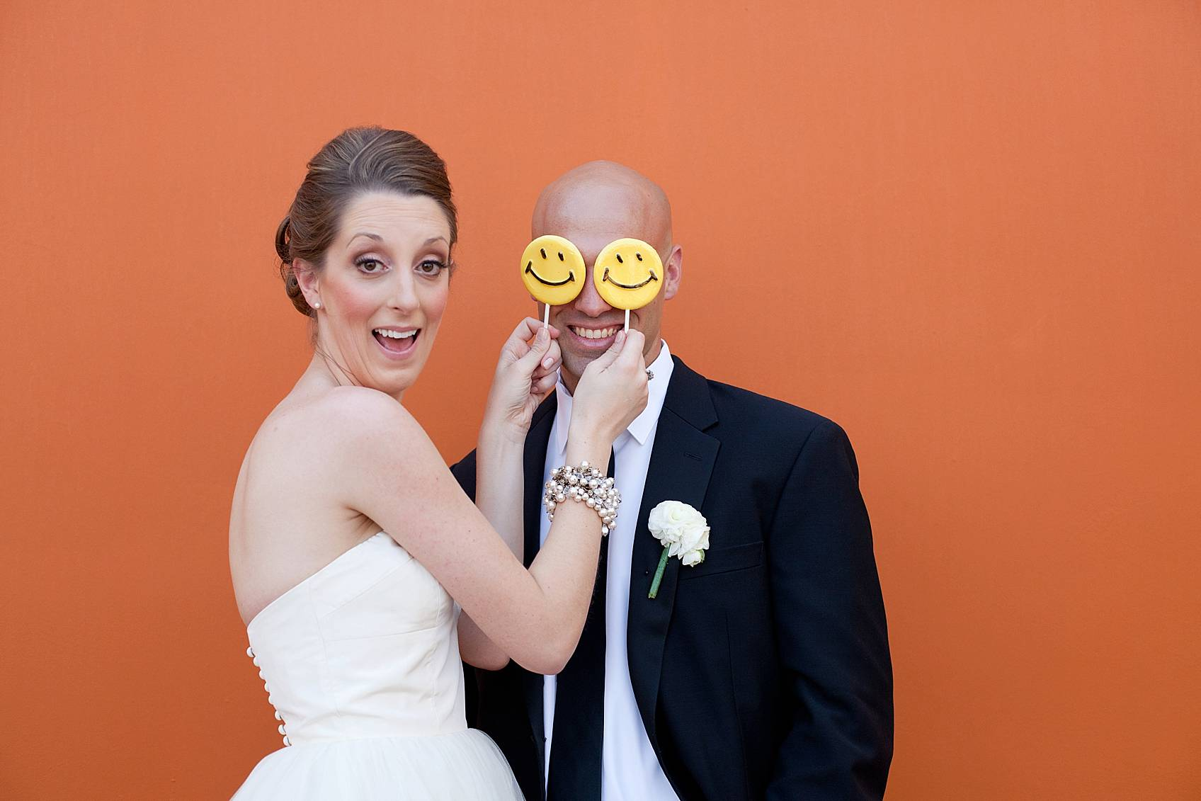 bride and groom goofing off with happy face lollipops