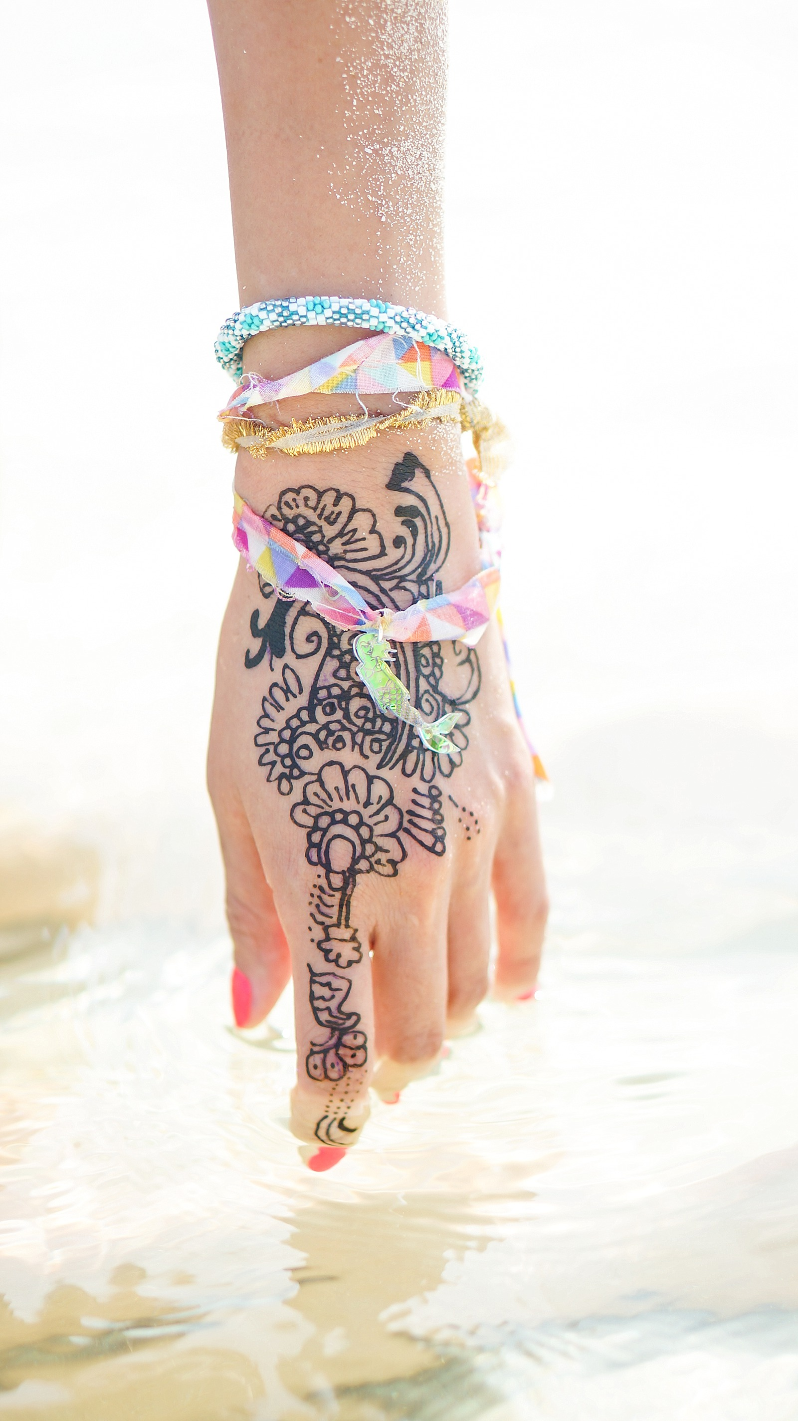 Hand in water covered in henna tattoo and mermaid bracelet floating in water in Thailand phi phi islands