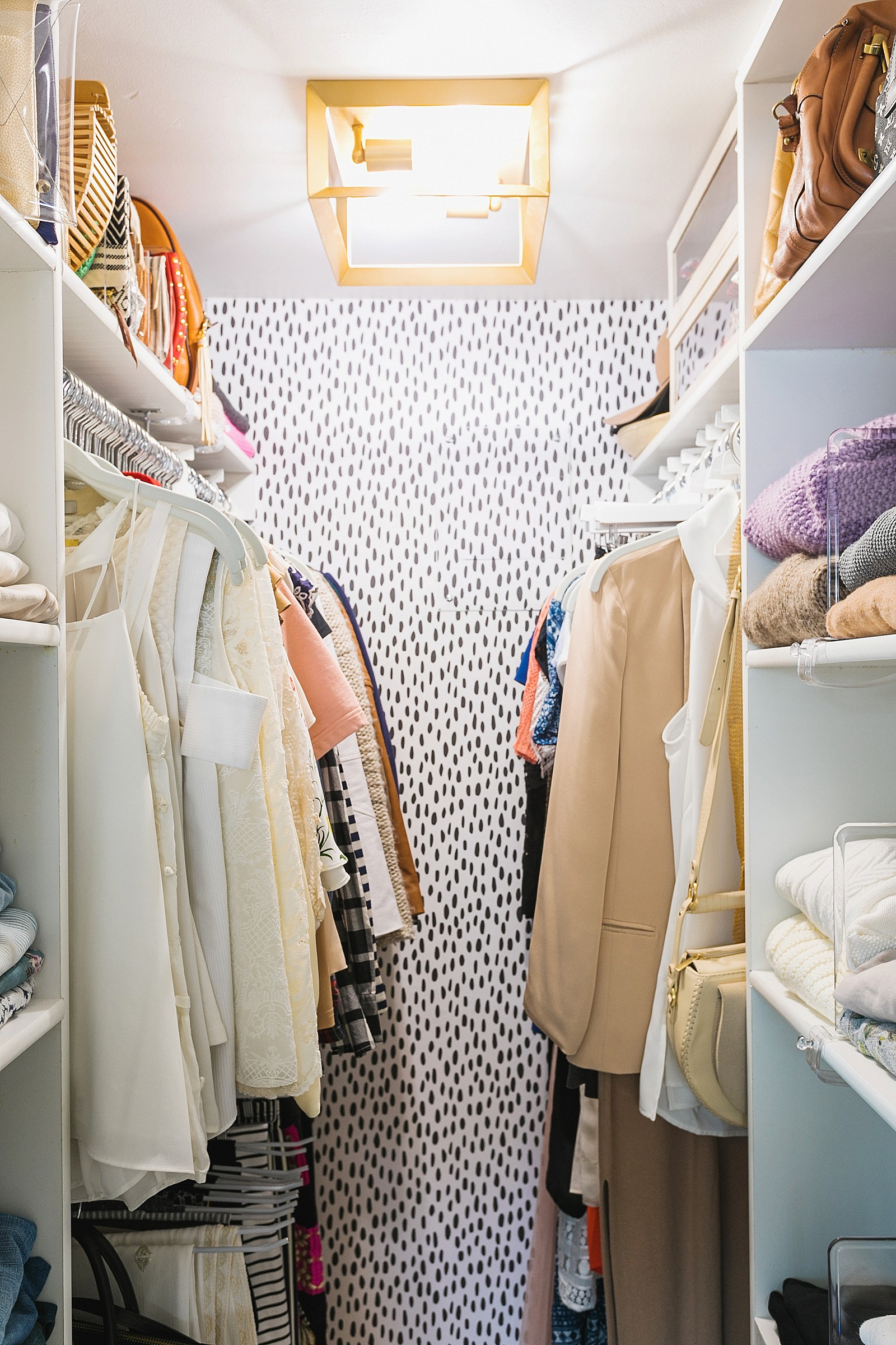 bright and very small tiny closet makeover featuring removable wallpaper and gold flush mount light in closet with ample shelving for sweaters and white hangers