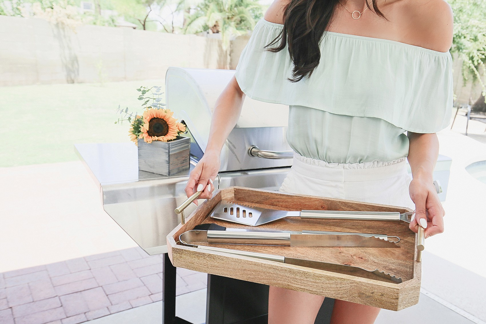 Diana Elizabeth blogger holding tray with bbq utensils in front of a bbq grill