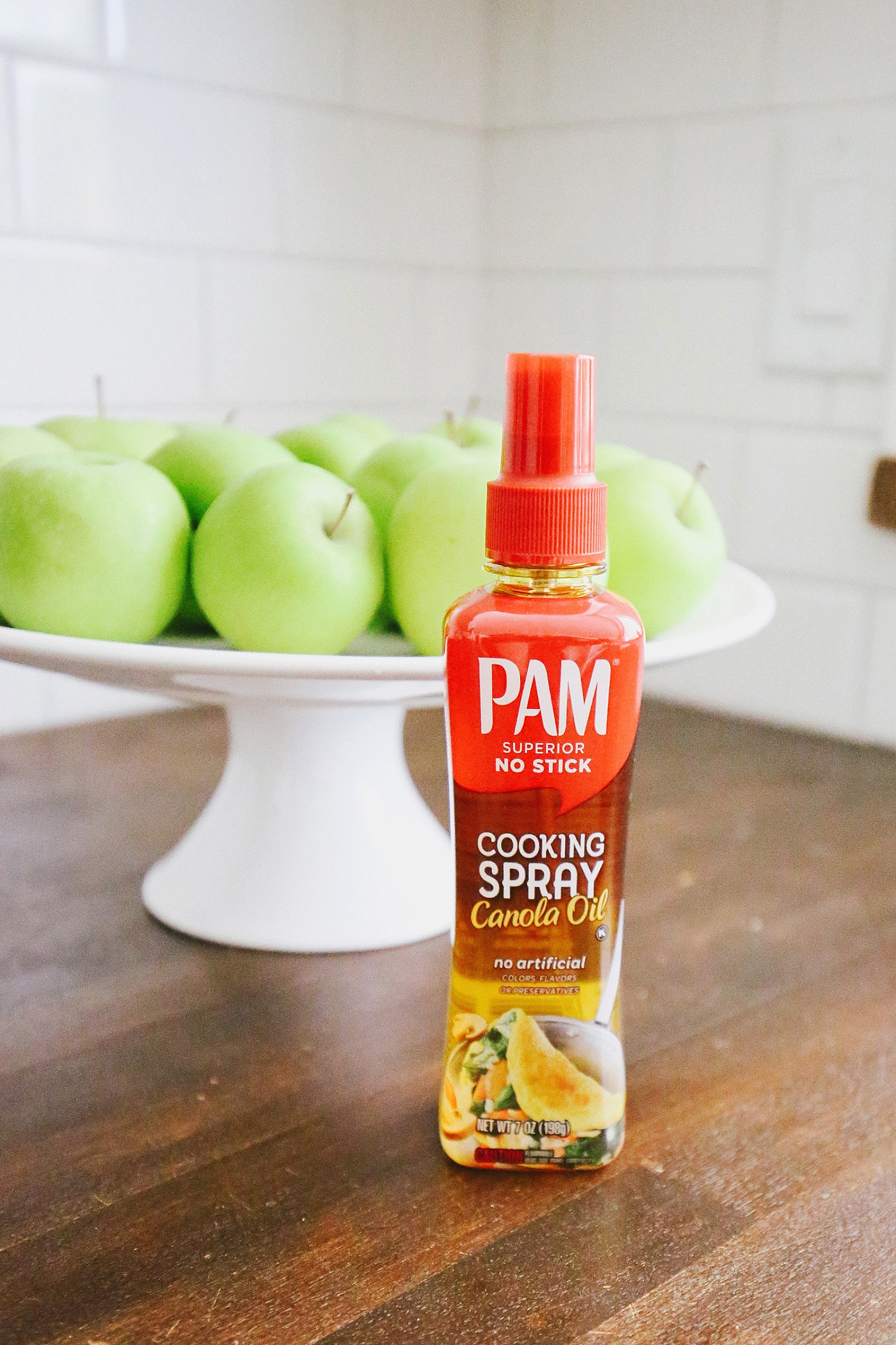 pam pump spray on kitchen countertop in front of green apples