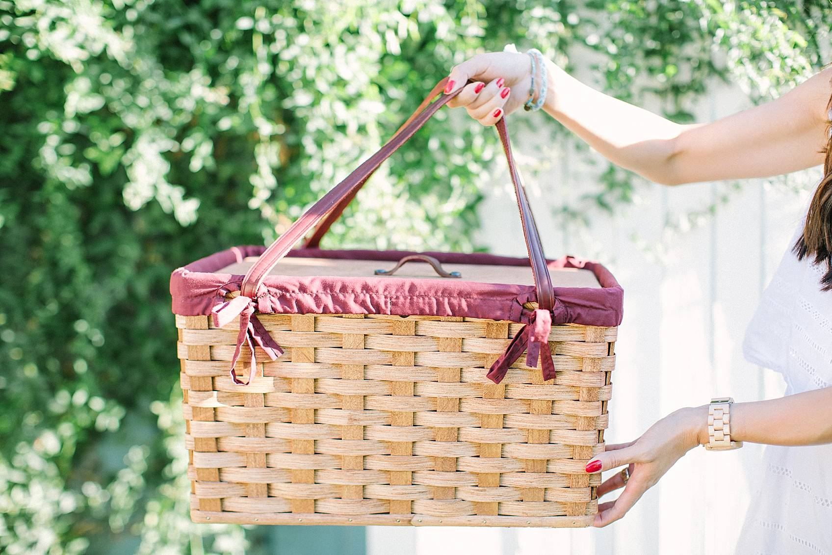 amish made picnic basket diana holding it infront of a white fence with green vines in background