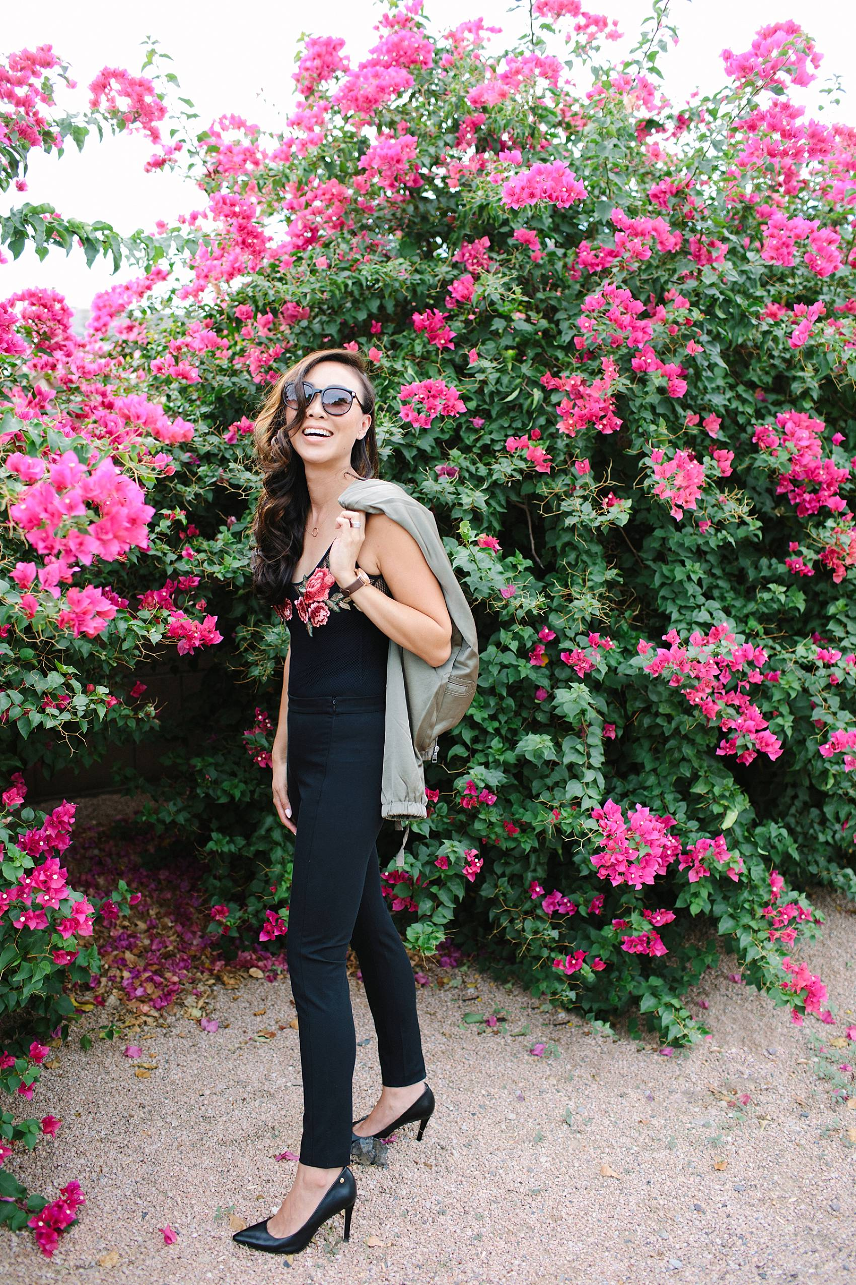 diana elizabeth lifestyle blogger in black devon-fit bi-stretch leggings and over shoulder holding satin bomber jacket by banana republic standing in front of pink bougevvilla plants wildfox sunglasses