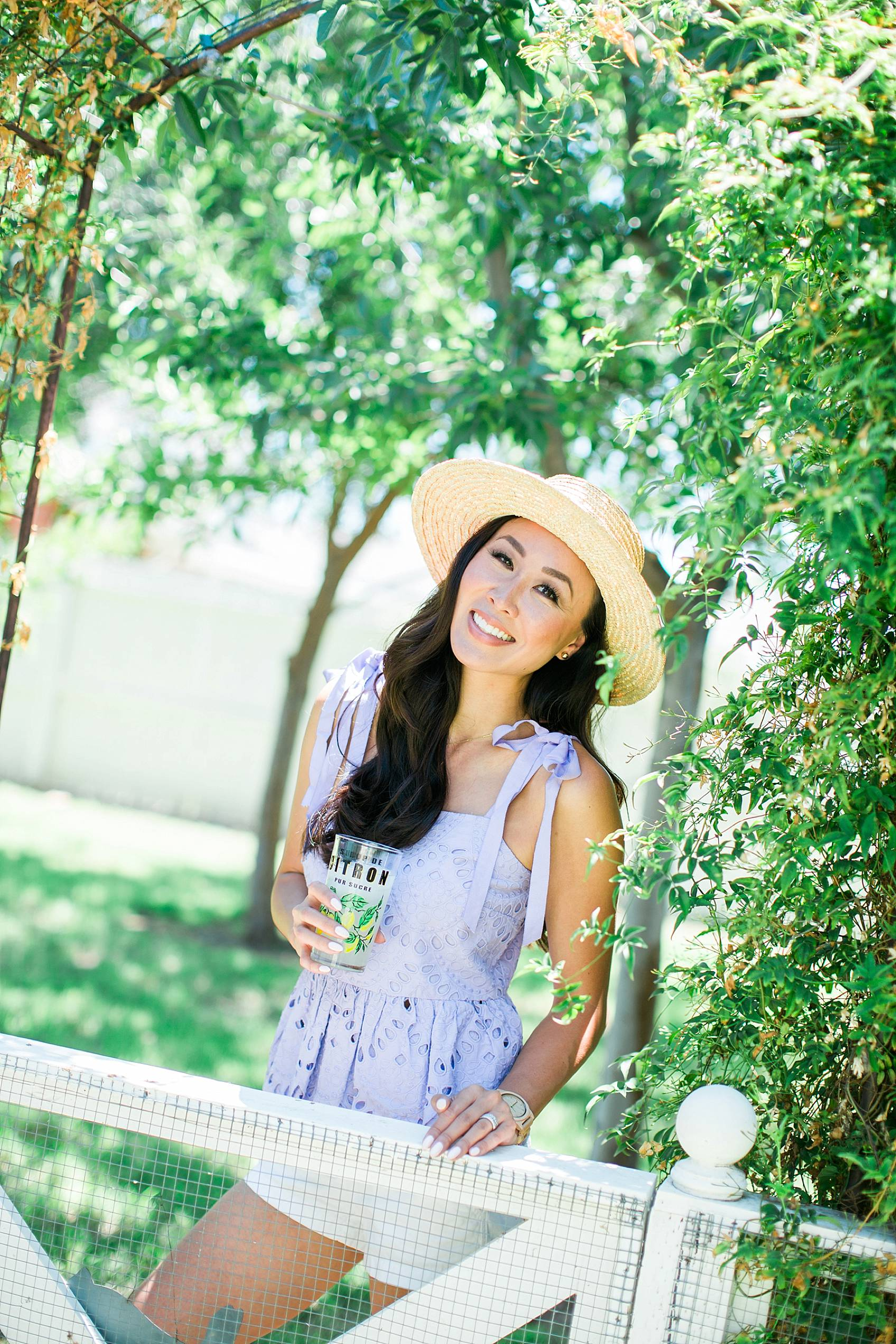 Lifestyle blogger diana elizabeth in purple eyelet top by j.crew in backyard jasmine vine wall holding glass of lemonade