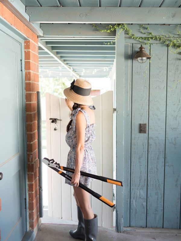 Gardener heading into the garden through white gate carrying Fiskars and wearing a romper