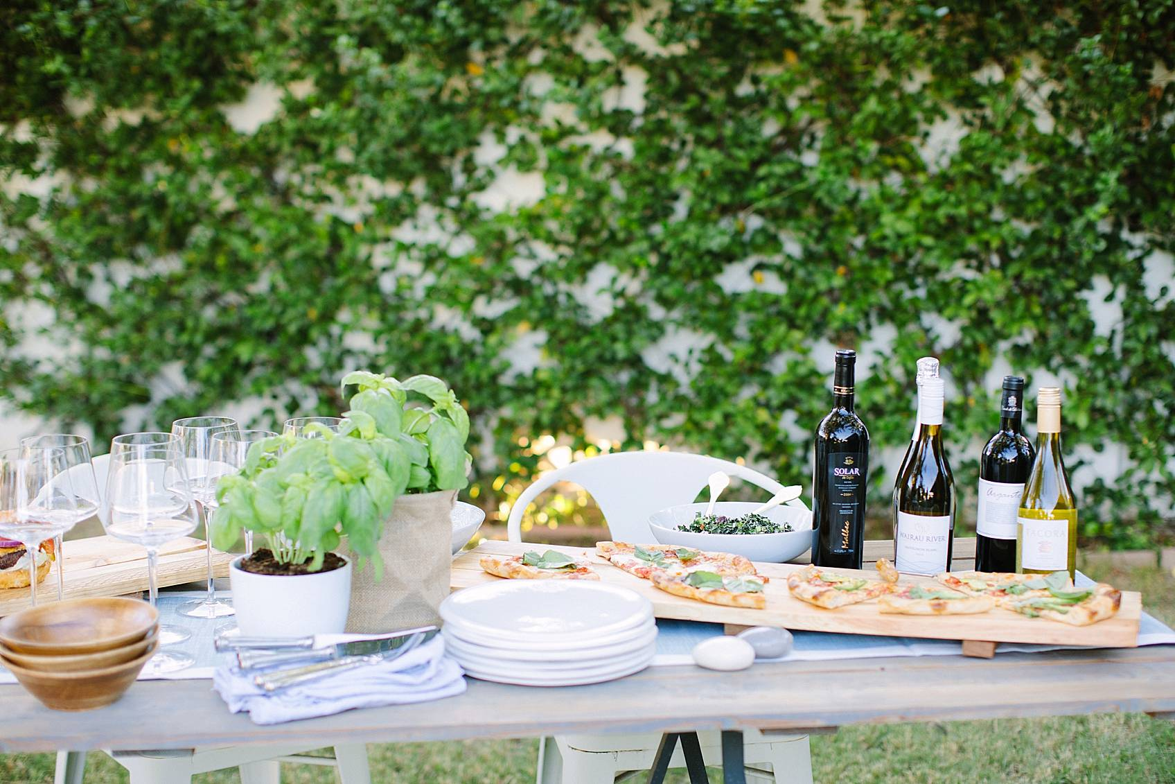 jasmine vine wall in background of set table featuring wine and boards of pizza and salad