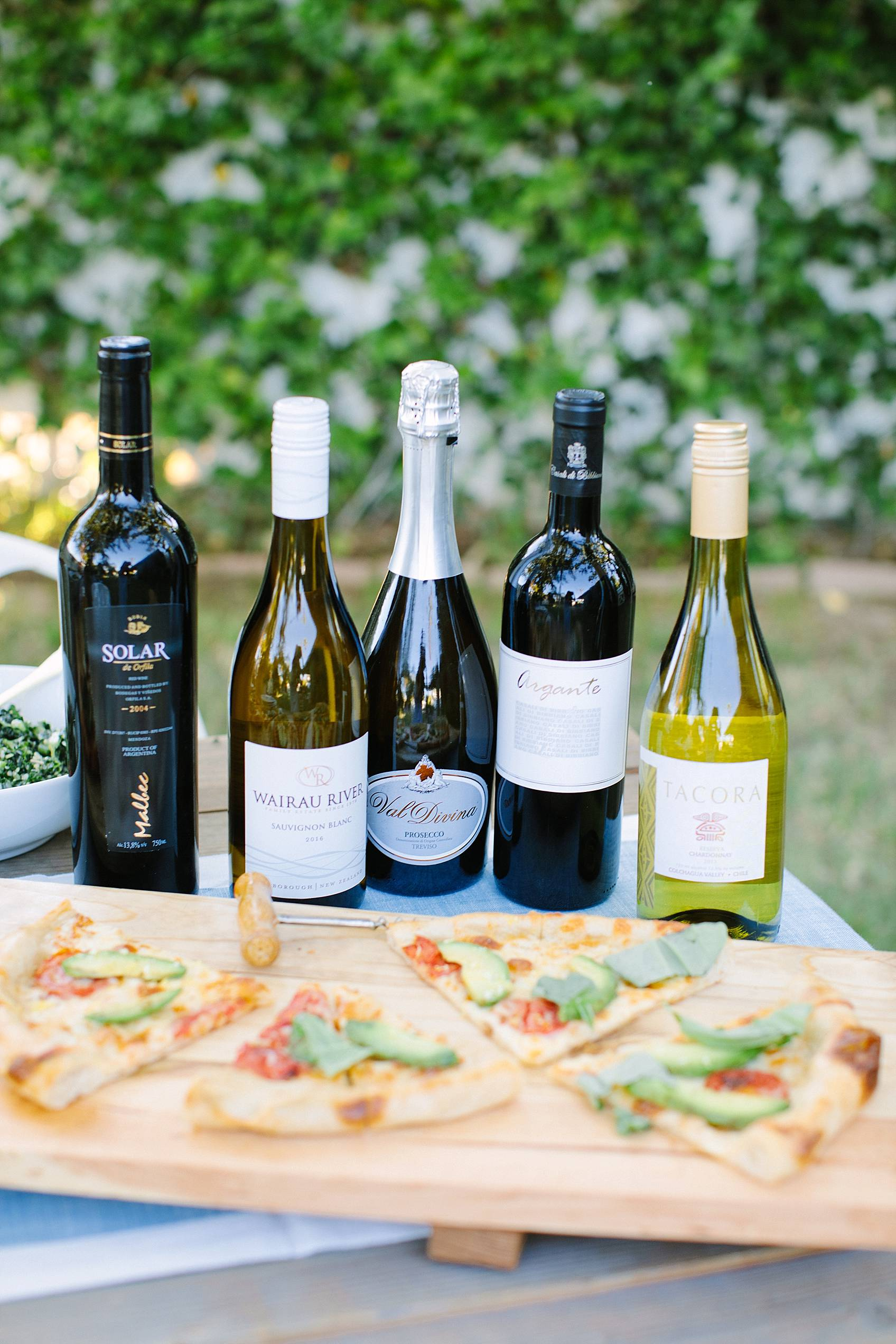 bottles of wine on table behind pizza featured from grapeswine.com