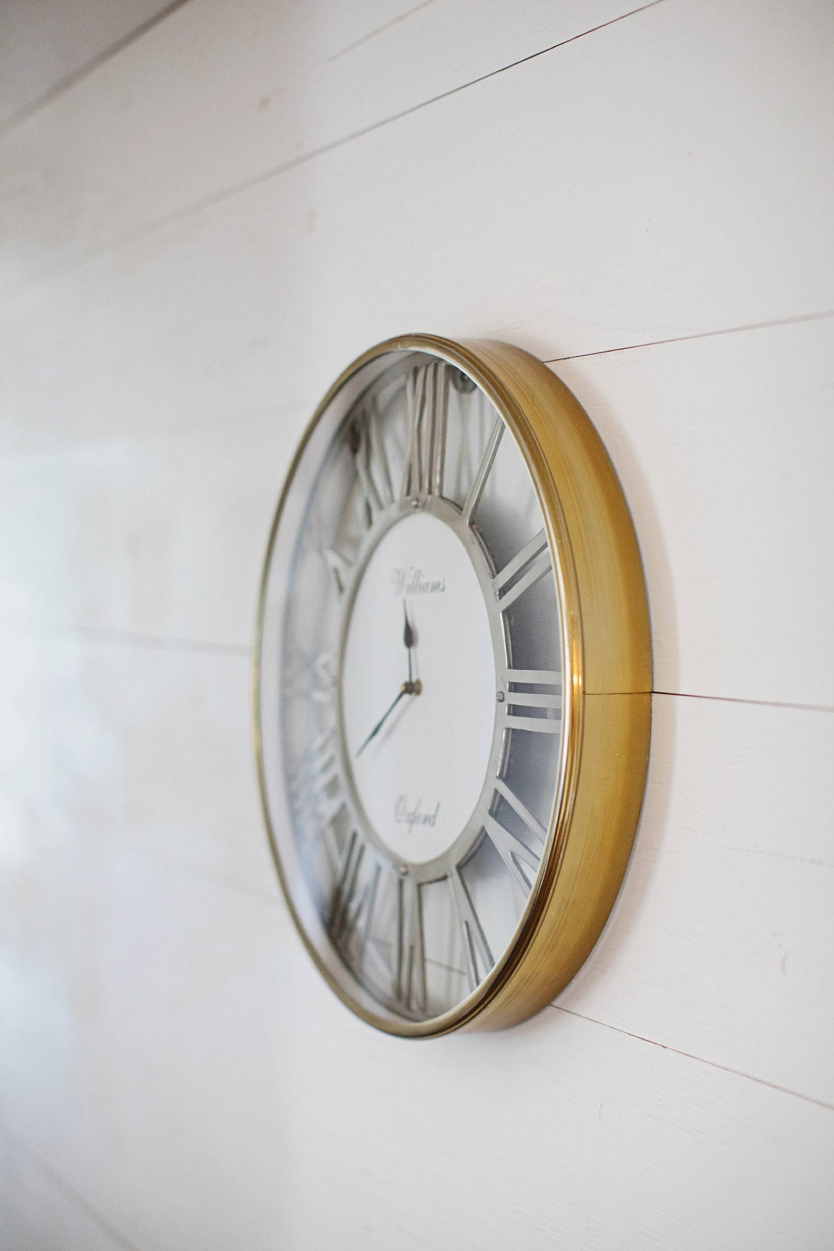 brass clock with silver numeral numbers on white shiplap wall to showcase boho home trend