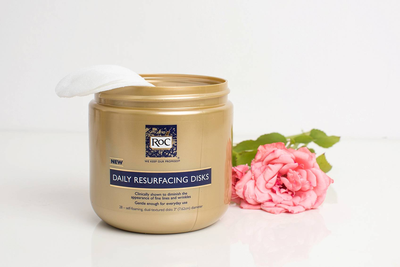 RoC products anti aging drugstore retinol products on display with pink rose facial discs