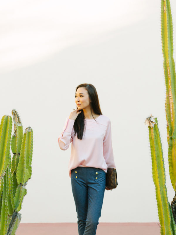 diana Elizabeth lifestyle blogger standing in front of white wall with cactus on both sides of her taken at heard museum in phoenix arizona