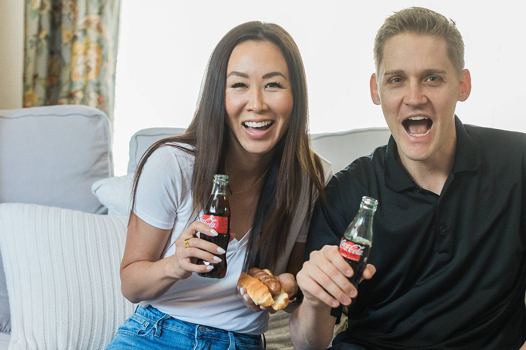 lifestyle blogger diana Elizabeth with husband on couch watching football - football party Coke Zero tailgating at home party setup ideas