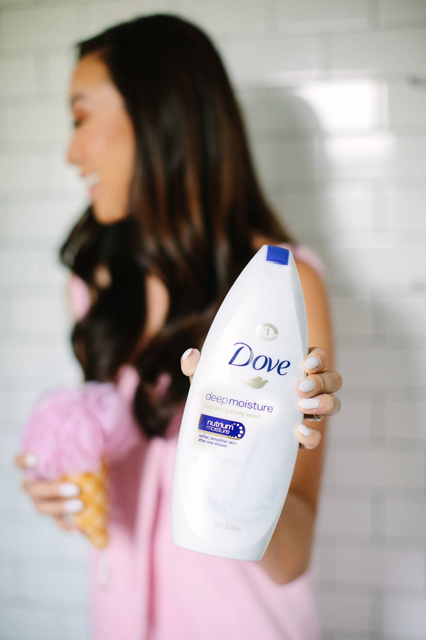 holding dove beauty wash in shower with ice cream body pouf