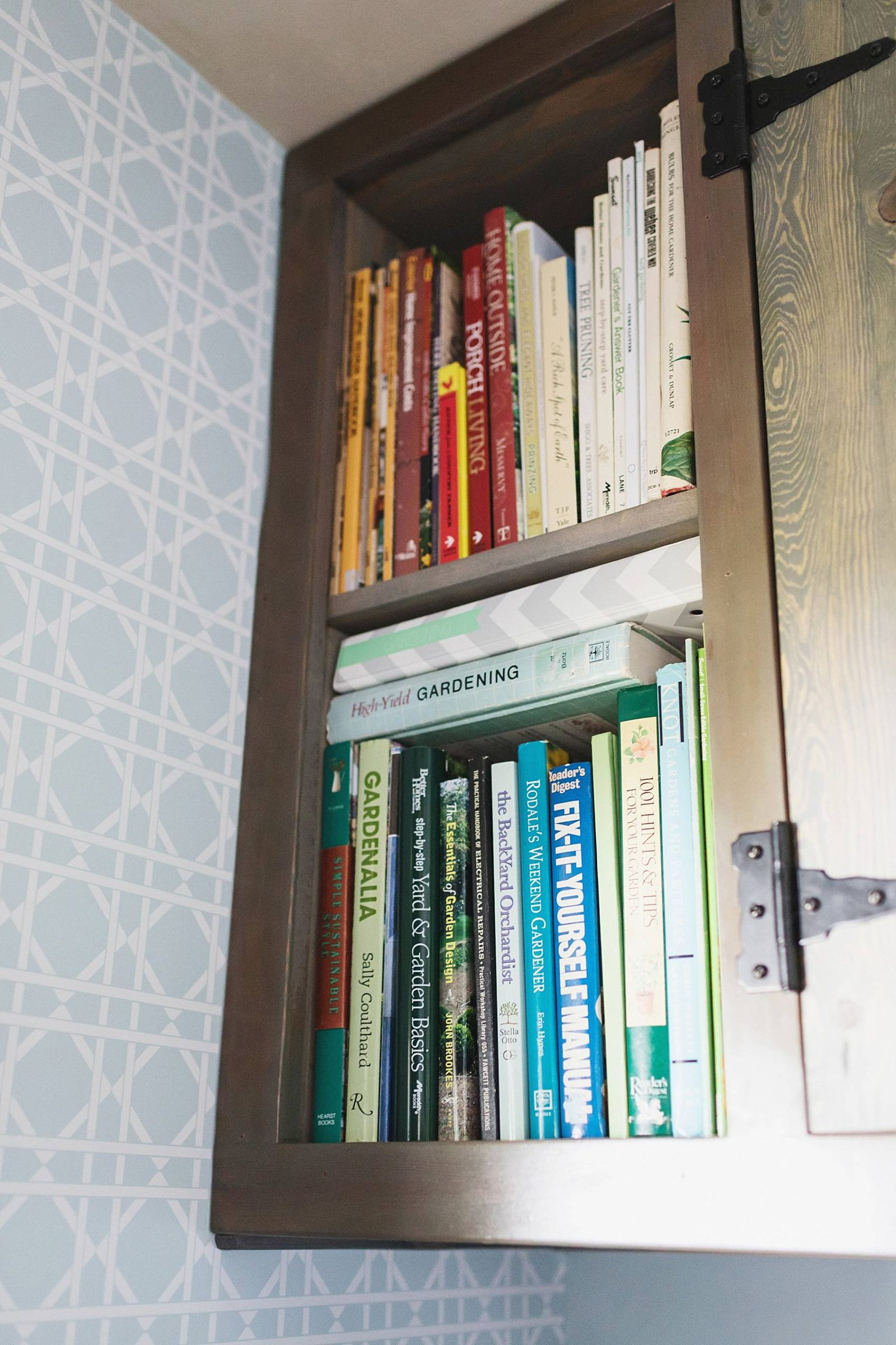 laundry mud room with custom cabinets rustic look with blue removable wallpaper in background and mint hunter fan gardening book shelf