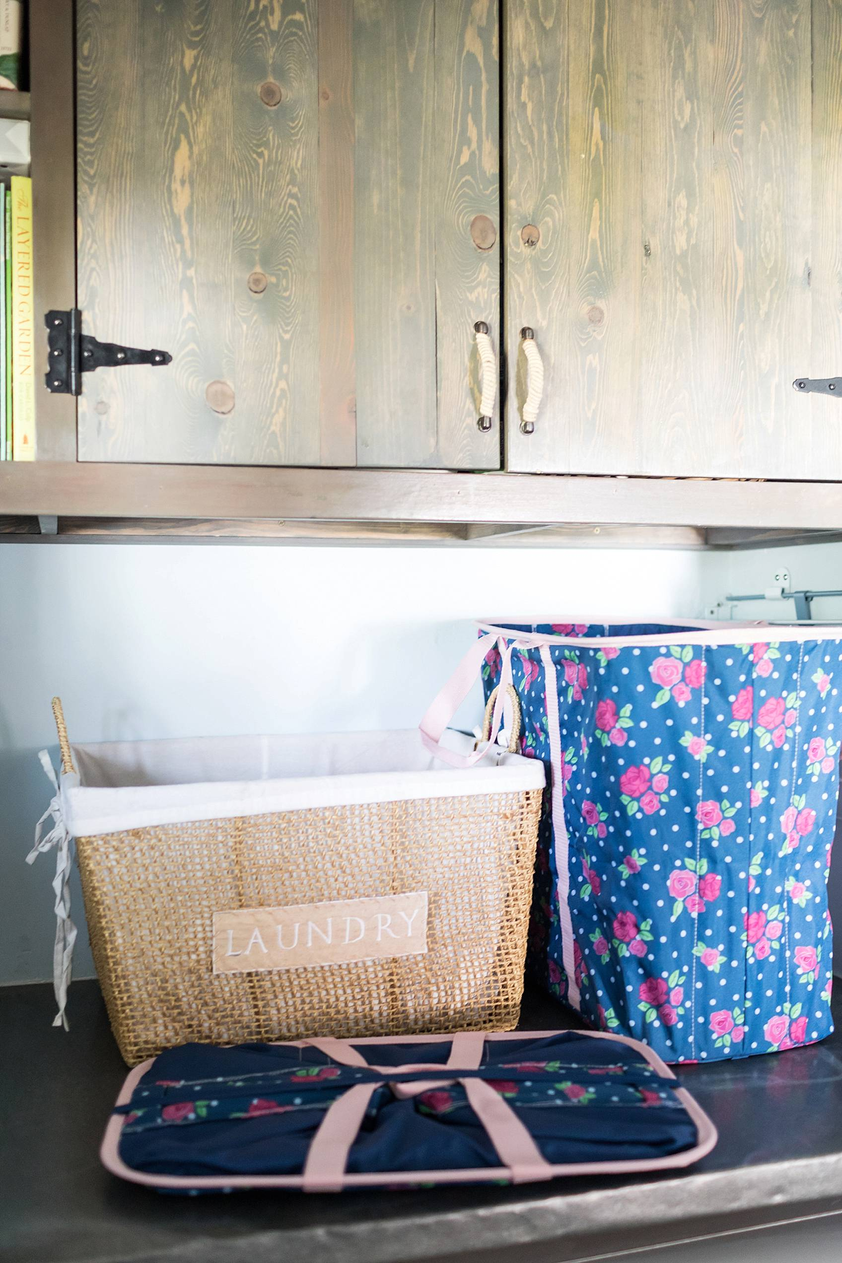 laundry mud room with custom cabinets rustic look with blue removable wallpaper in background and mint hunter fan Ikea cactus hunter boots display laundry basket cute rose collapsible
