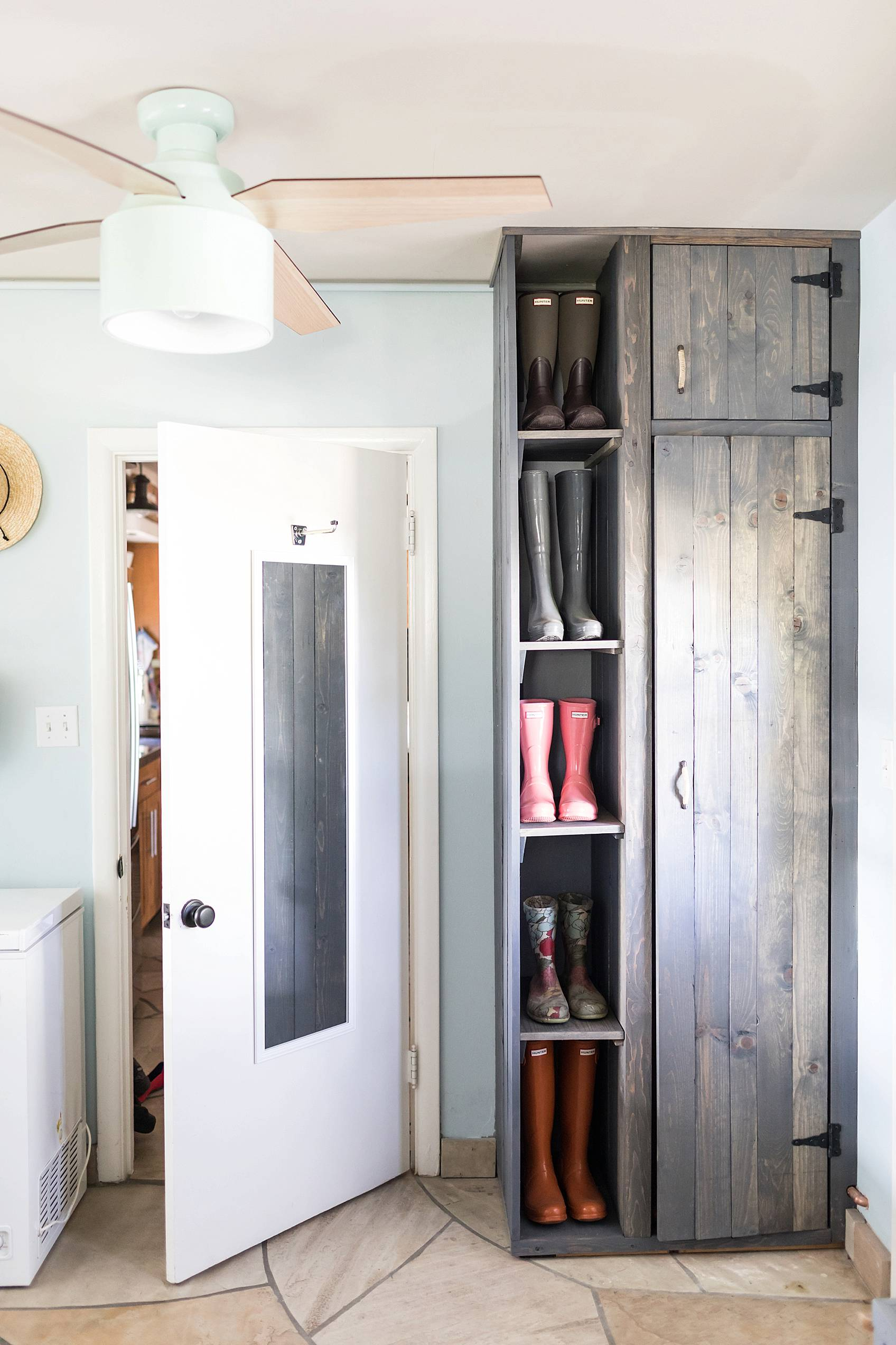 laundry mud room with custom cabinets rustic look with blue removable wallpaper in background and mint hunter fan Ikea cactus hunter boots display