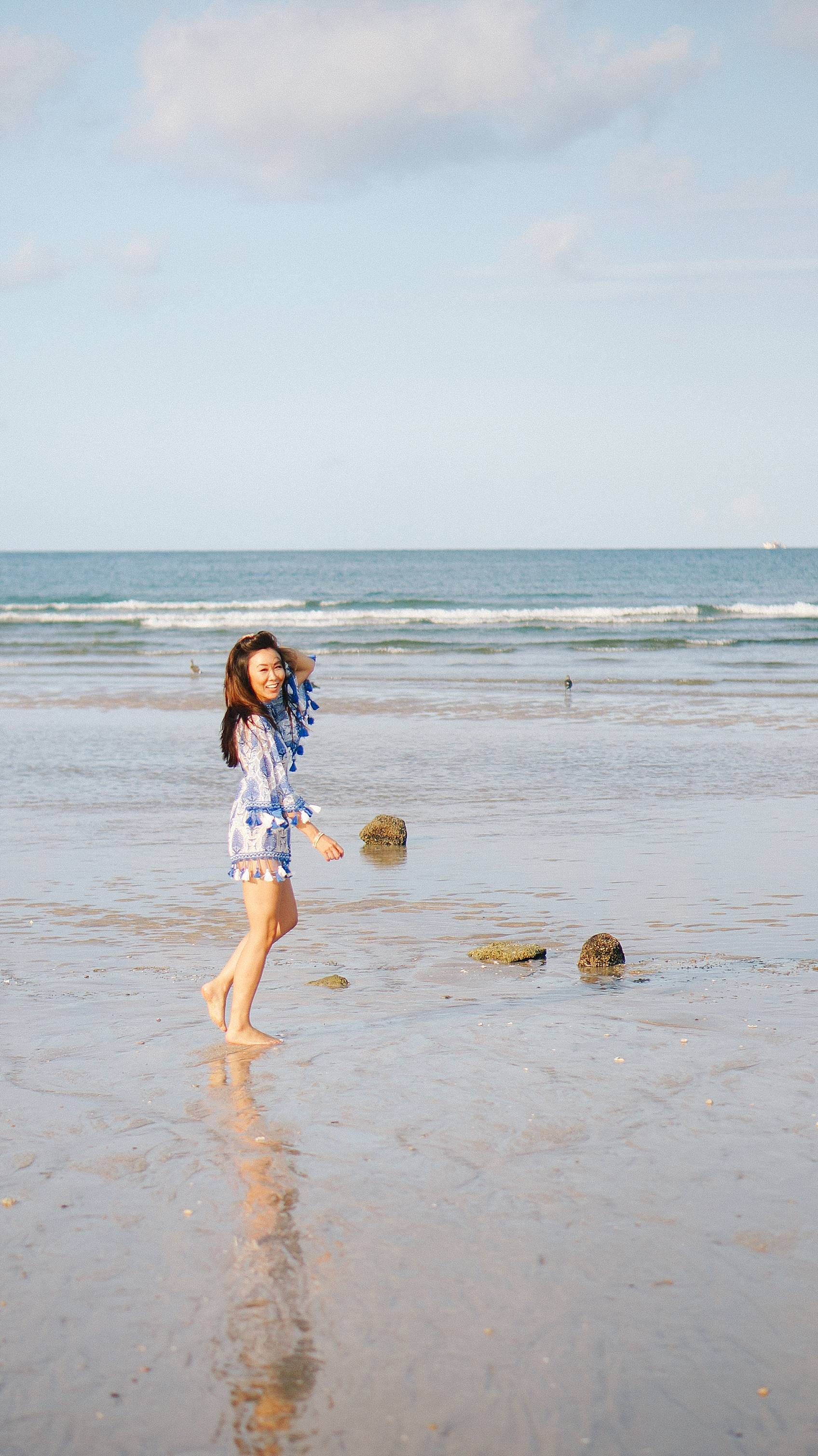 Lifestyle blogger Diana Elizabeth in Puerto Penasco Rocky Point Mexico in water wearing blue and white tassel romper
