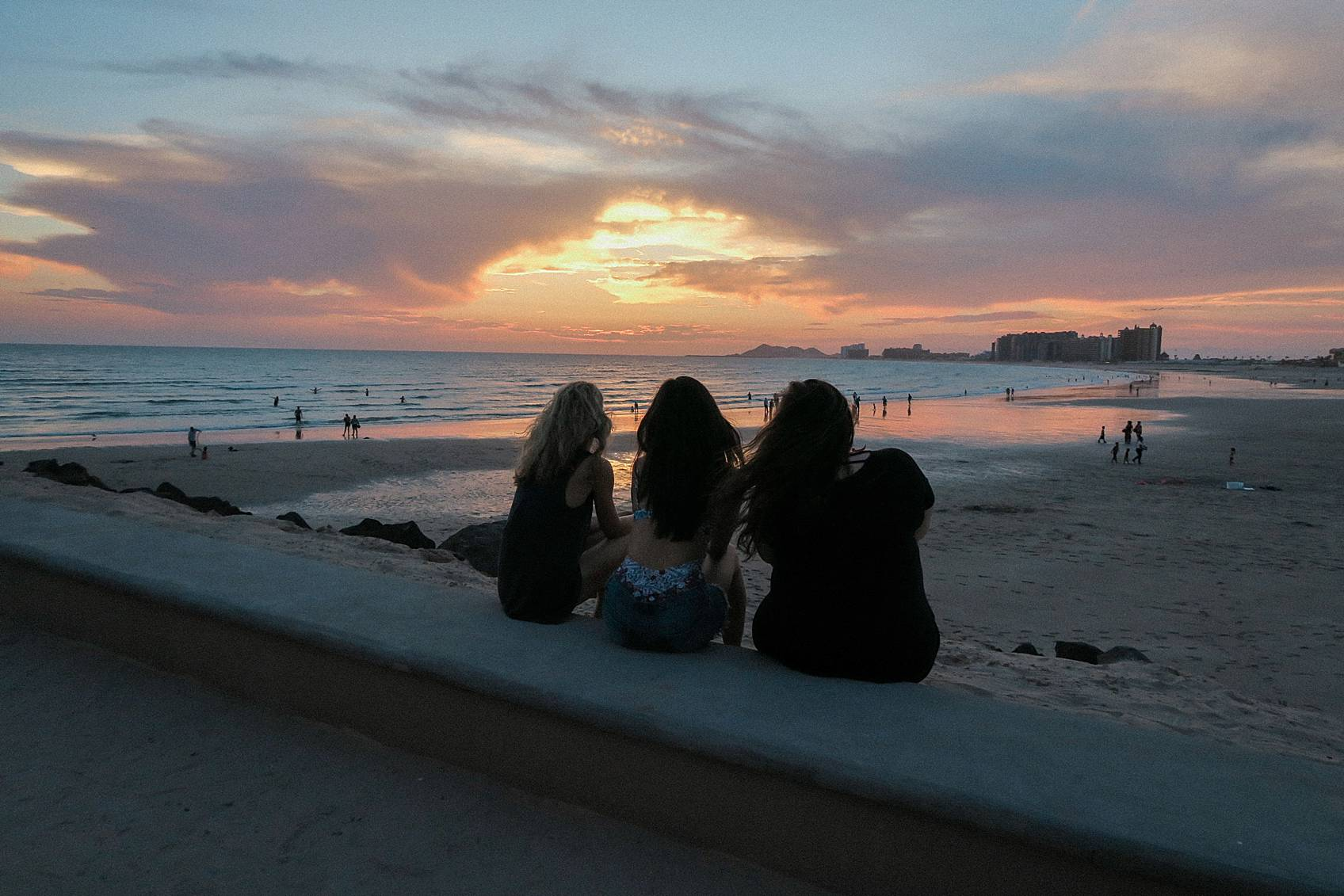 three friends silhouette sitting on ledge watching sunset at rocky point Puerto penance Mexico