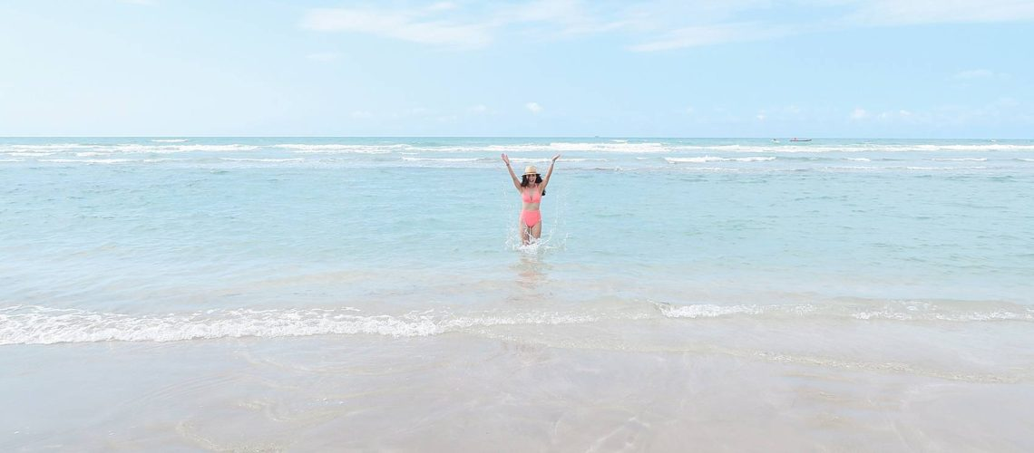 Lifestyle blogger Diana Elizabeth in Puerto Penasco Rocky Point Mexico in water wearing hot pink high waist bikini