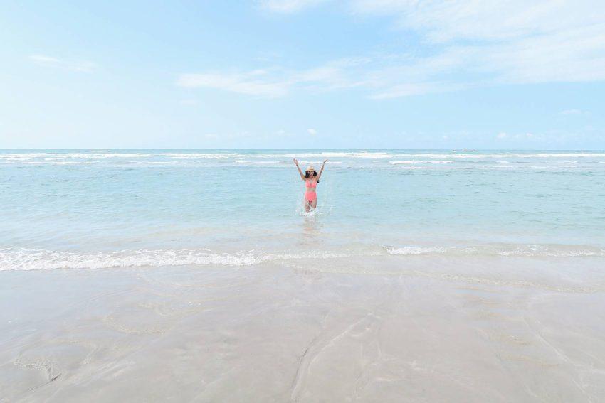 Lifestyle blogger Diana Elizabeth in Puerto Penasco Rocky Point Mexico in water wearing hot pink high waist bikini