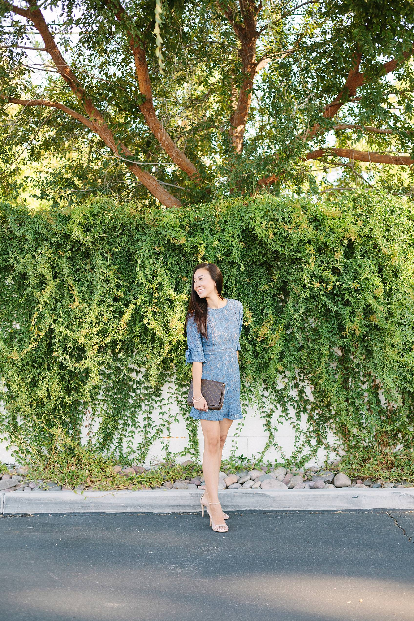 blue lace dress on lifestyle blogger diana elizabeth against cats claw vines