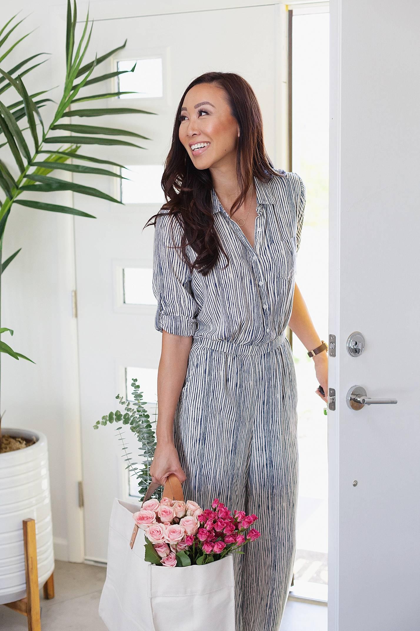 stripe jumpsuit walking in door of home with flowers in tote