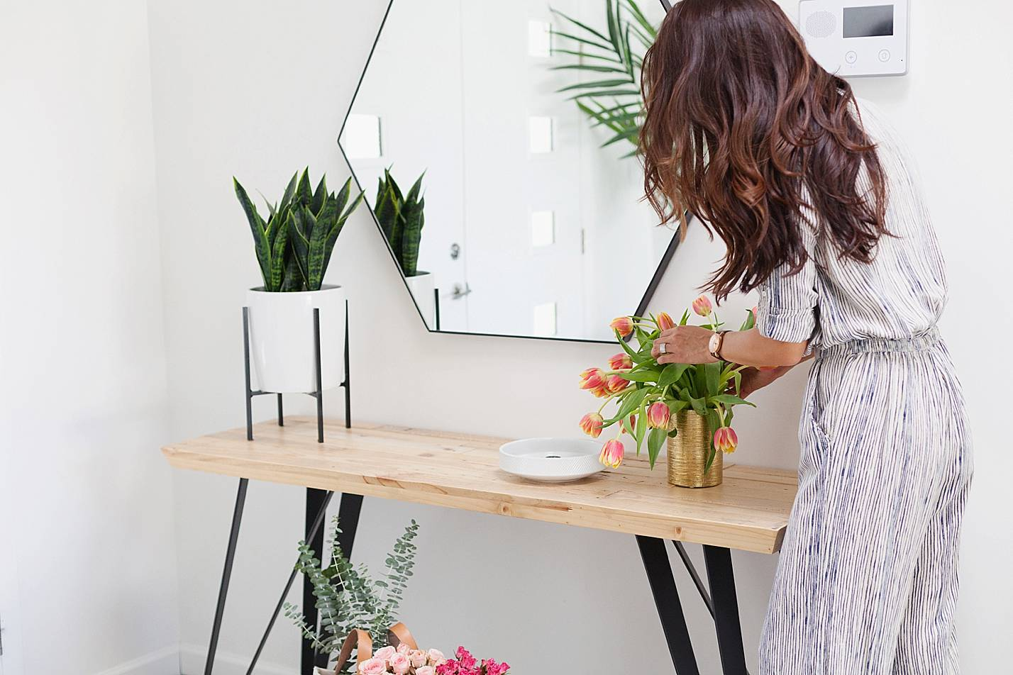 lifestyle shot rearranging flowers on console table in stripe jumpsuit
