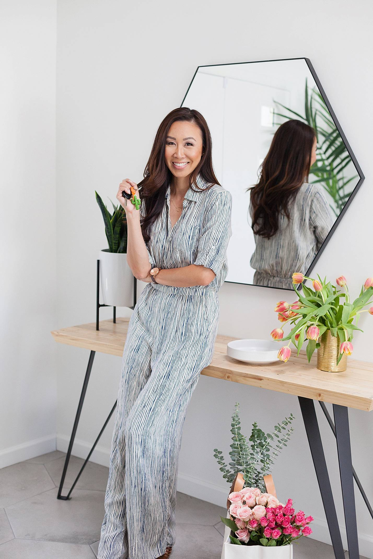 leaning up against console table in stripe jumpsuit holding keys about rental insurance