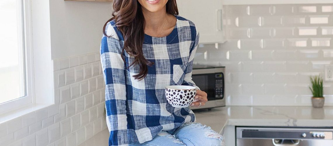 blue white checker top anthropology ripped jeans sitting on top of kitchen counter