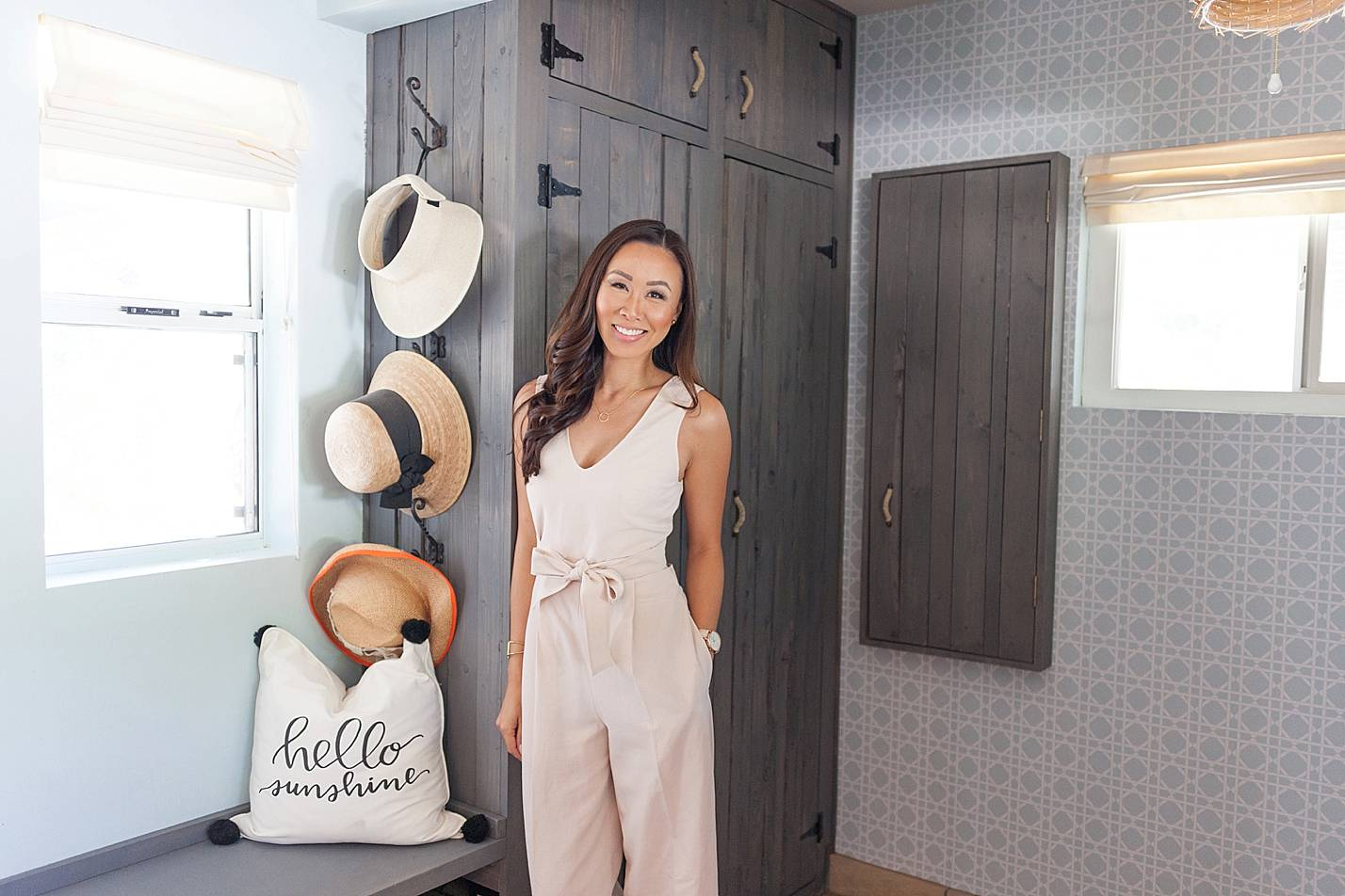 blush jumpsuit from club Monaco standing in mudroom laundry room garden hats in back and removable wallpaper