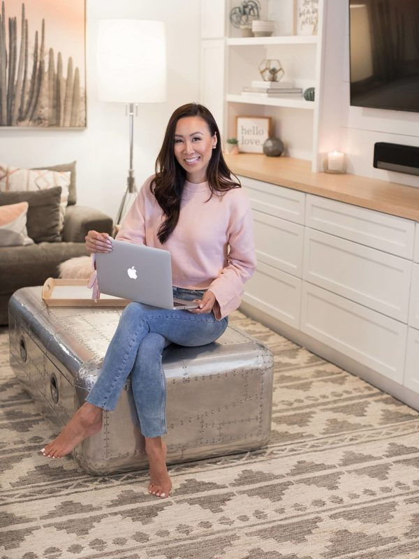 pink sweater ankle jeans sitting on coffee table Wireless router by Norton Core security fits well into home decor