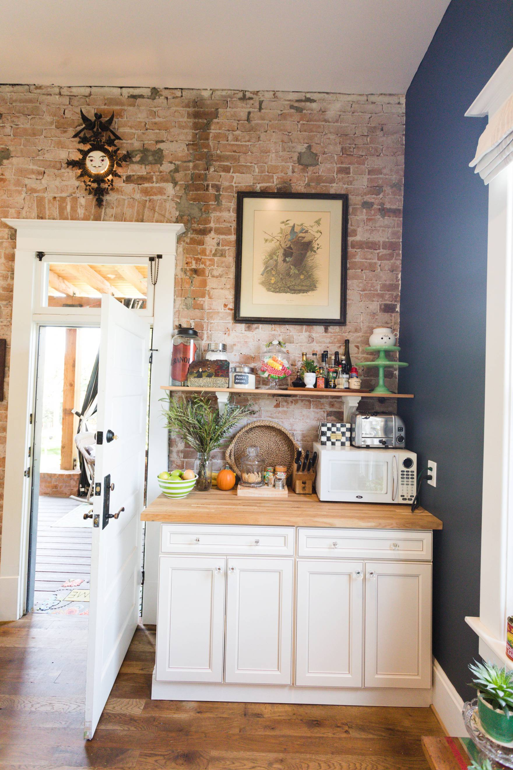 Home Tour of Boho Farm and Home in Downtown Phoenix - cottage brick style home from 1903 living room to kitchen details, exposed brick transom above the doors