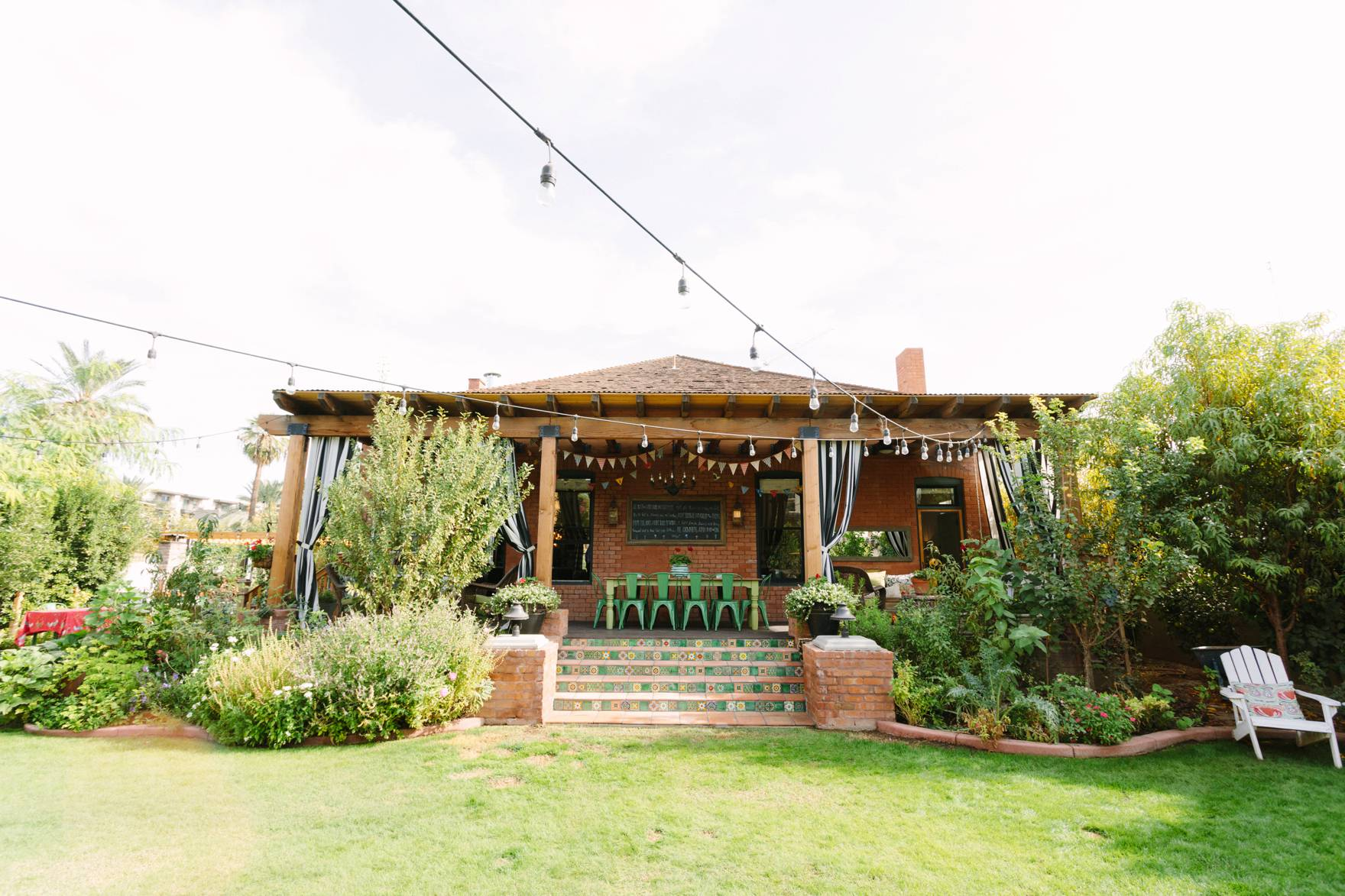 Home Tour of Boho Farm and Home in Downtown Phoenix - cottage brick style home from 1903 back porch bunt flags and casual seating, outdoor curtains
