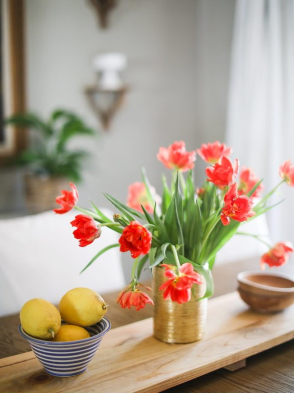 orange tulips in a gold vase