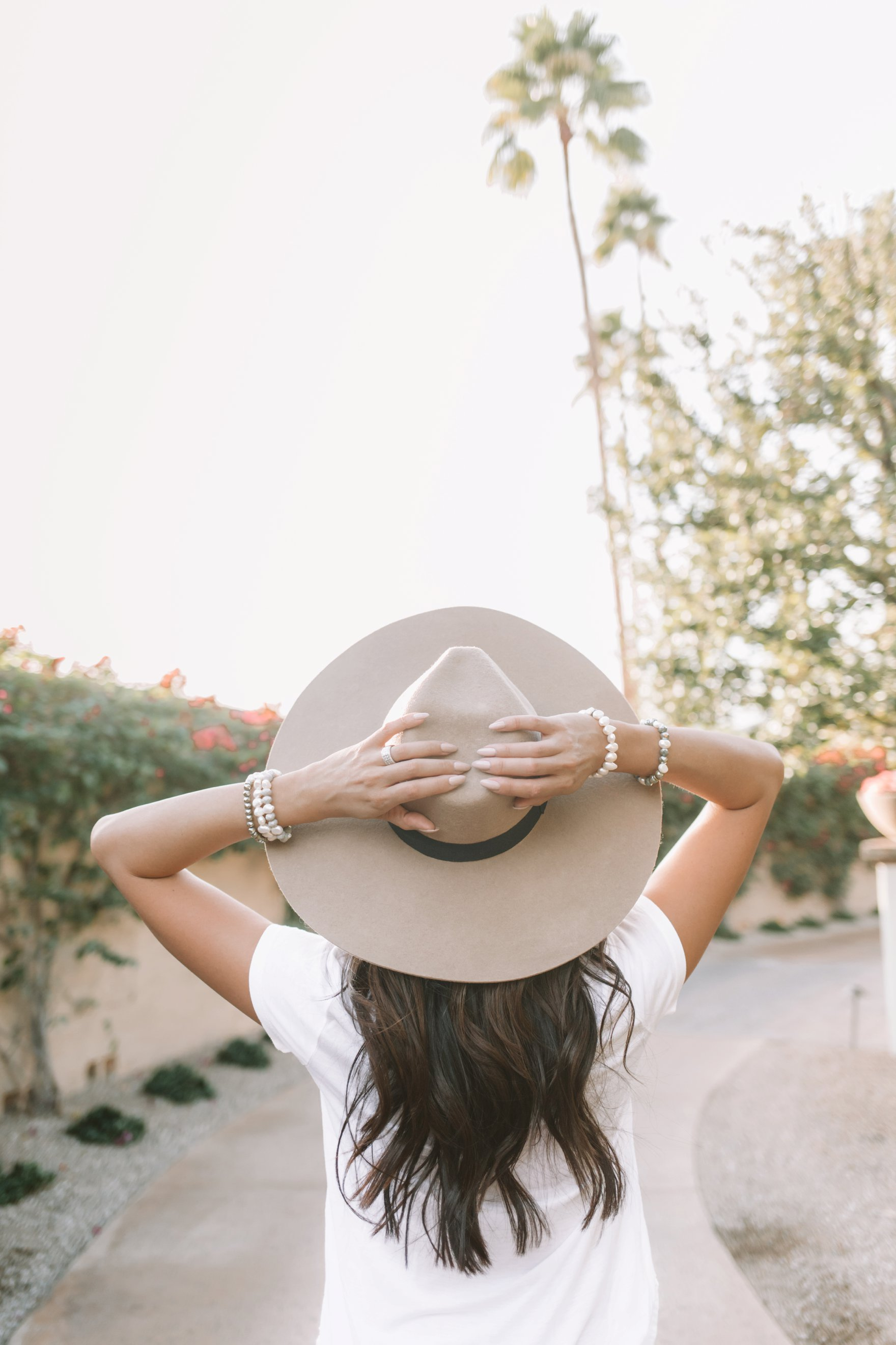 big felt hat with basic tee shirt and pearl necklaces. lifestyle style blogger Diana Elizabeth placing hands on back of hat