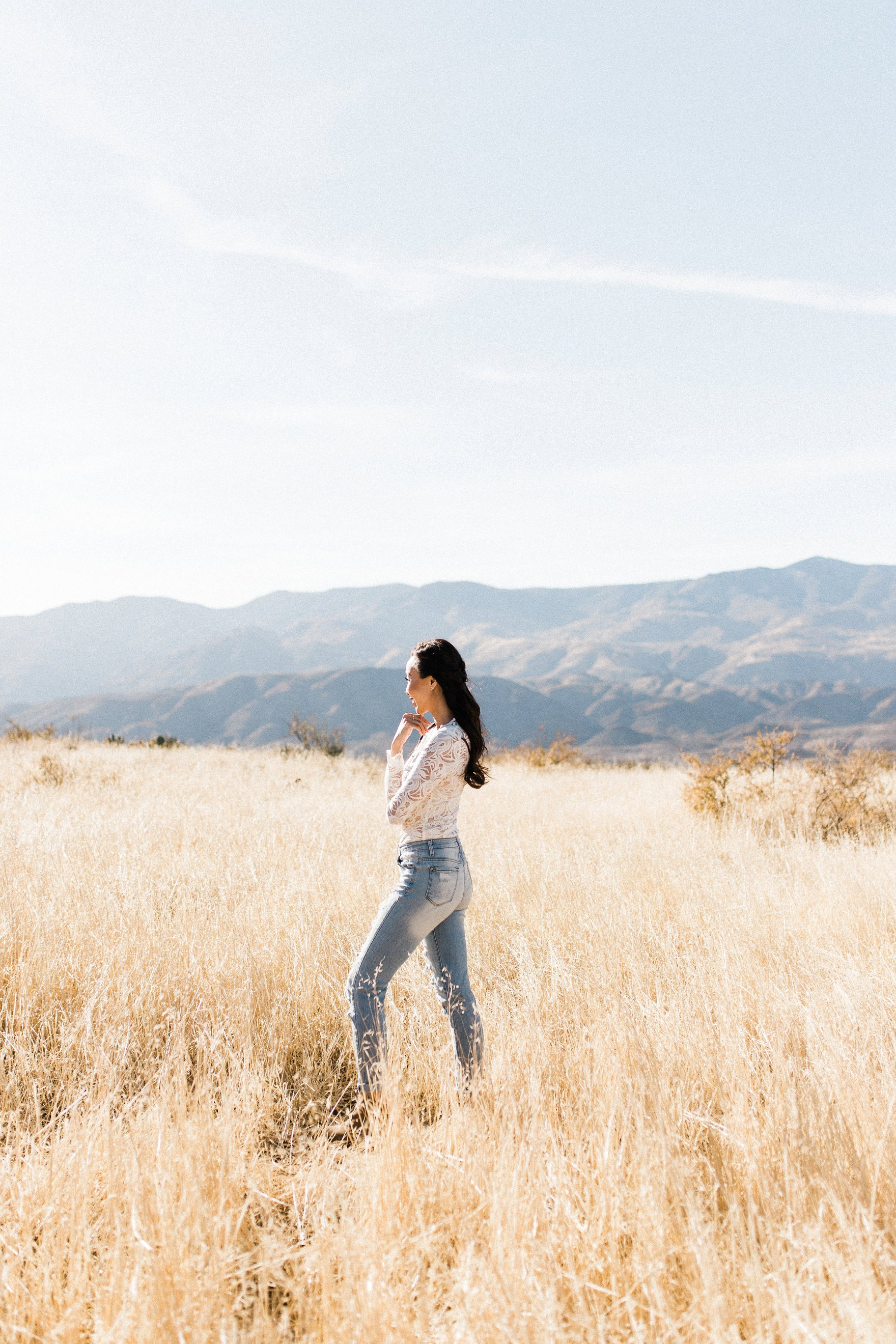 wind in hair white lace bodysuit high waist ripped jeans in a field Diana Elizabeth blogger photography by Autumn Renae Wide angle phoenix arizona