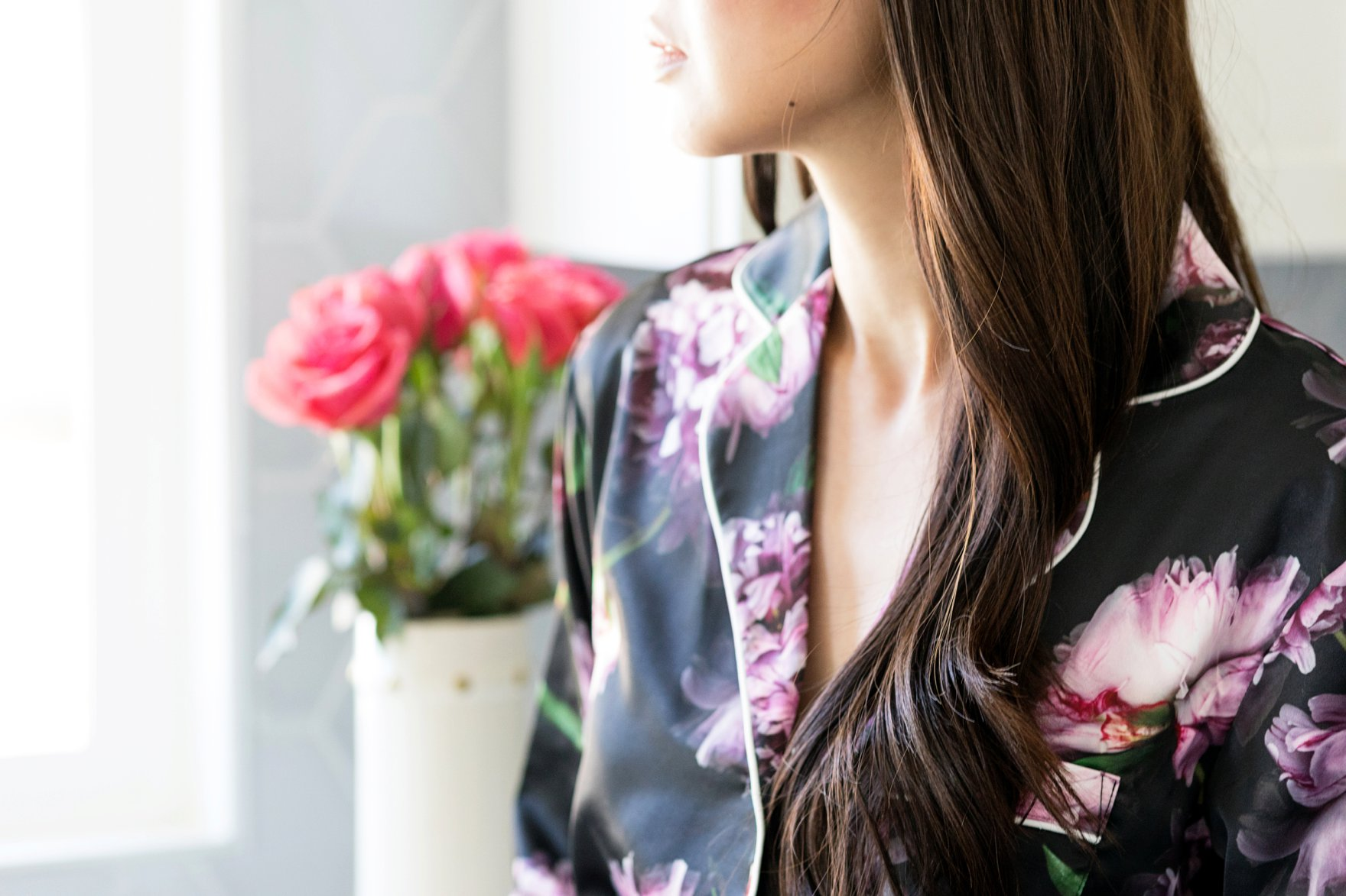 Diana Elizabeth blogger in bright white kitchen wearing Phoebe saatin belted pyjama set exclusive to figleaves - purple florals on black satin with a belt