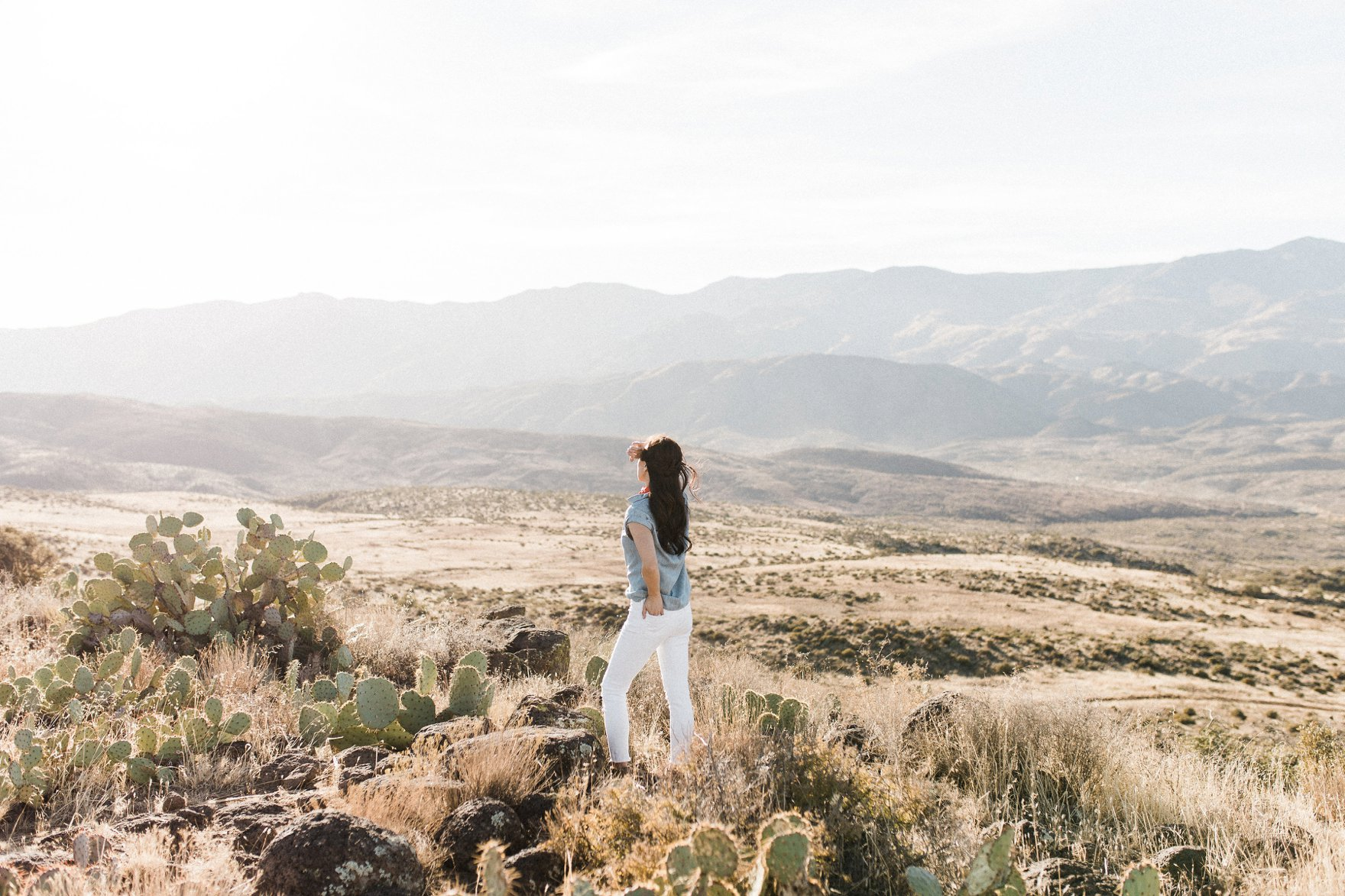 chambray short sleeved shirt white jeans with booties in tall dry grass in the arizona phoenix desert wearing looking out at the landscape explorer traveler