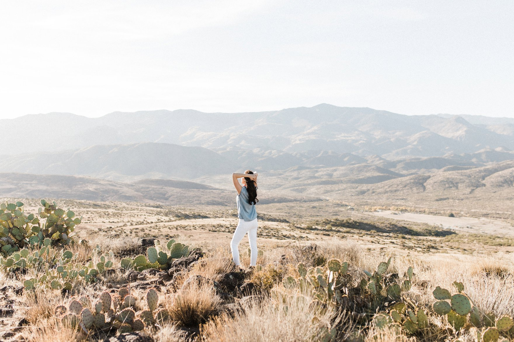 chambray short sleeved shirt white jeans with booties in tall dry grass in the arizona phoenix desert wearing looking out at the landscape