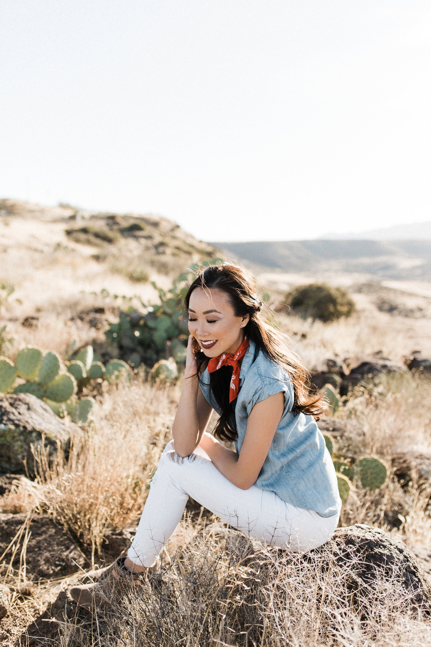 chambray short sleeved shirt white jeans with booties in tall dry grass in the arizona phoenix desert wearing red scarf around neck