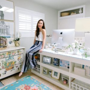 blogger photographer home office decor Diana Elizabeth - wearing white top with blue and white stripe pants sitting on Coastal Living by Stanley Furniture Oasis Cape Dutch Writing Desk