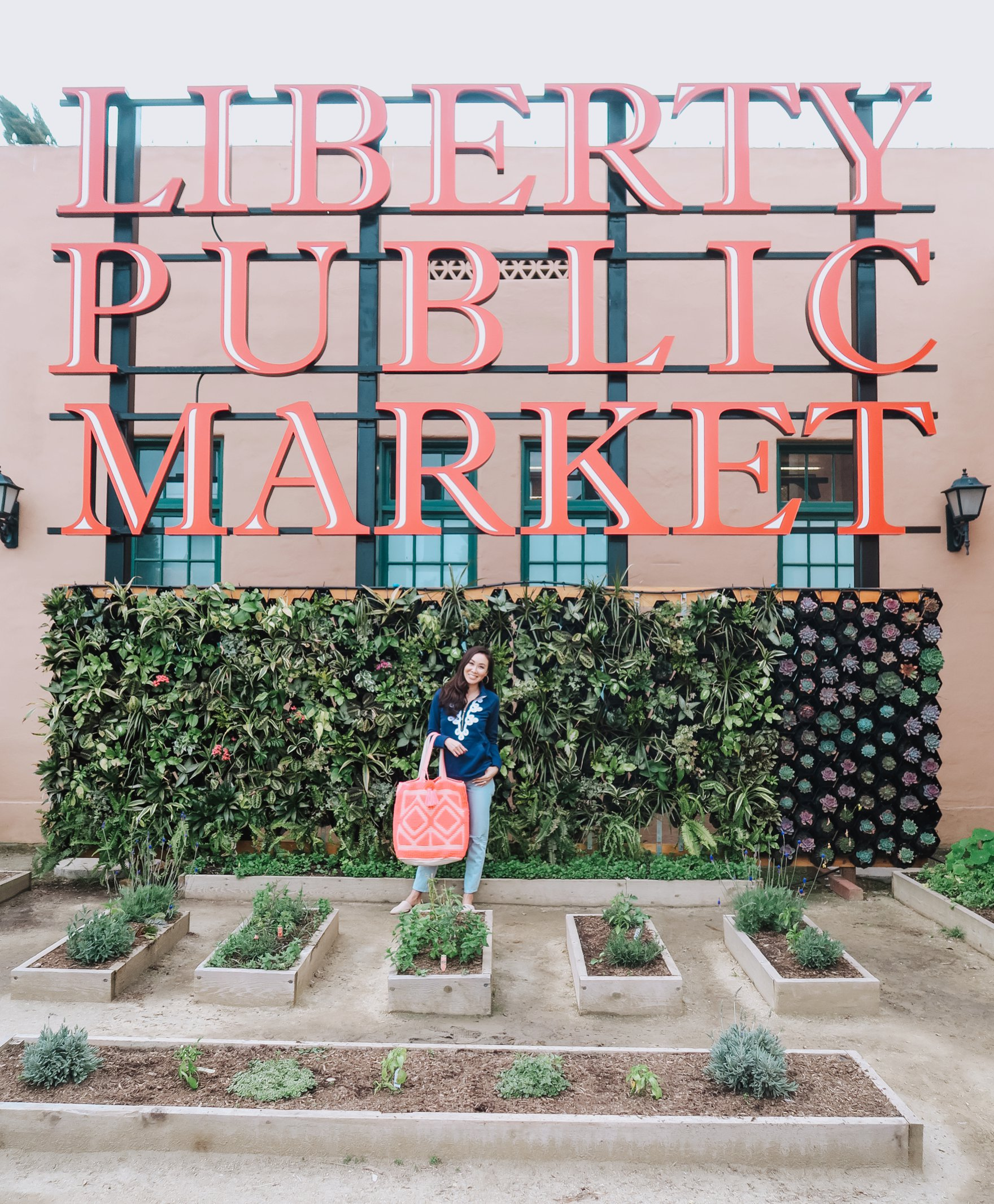 navy Lilly pulitzer pullover with bright pink tote on blogger Diana Elizabeth in San Diego at Liberty Public Market
