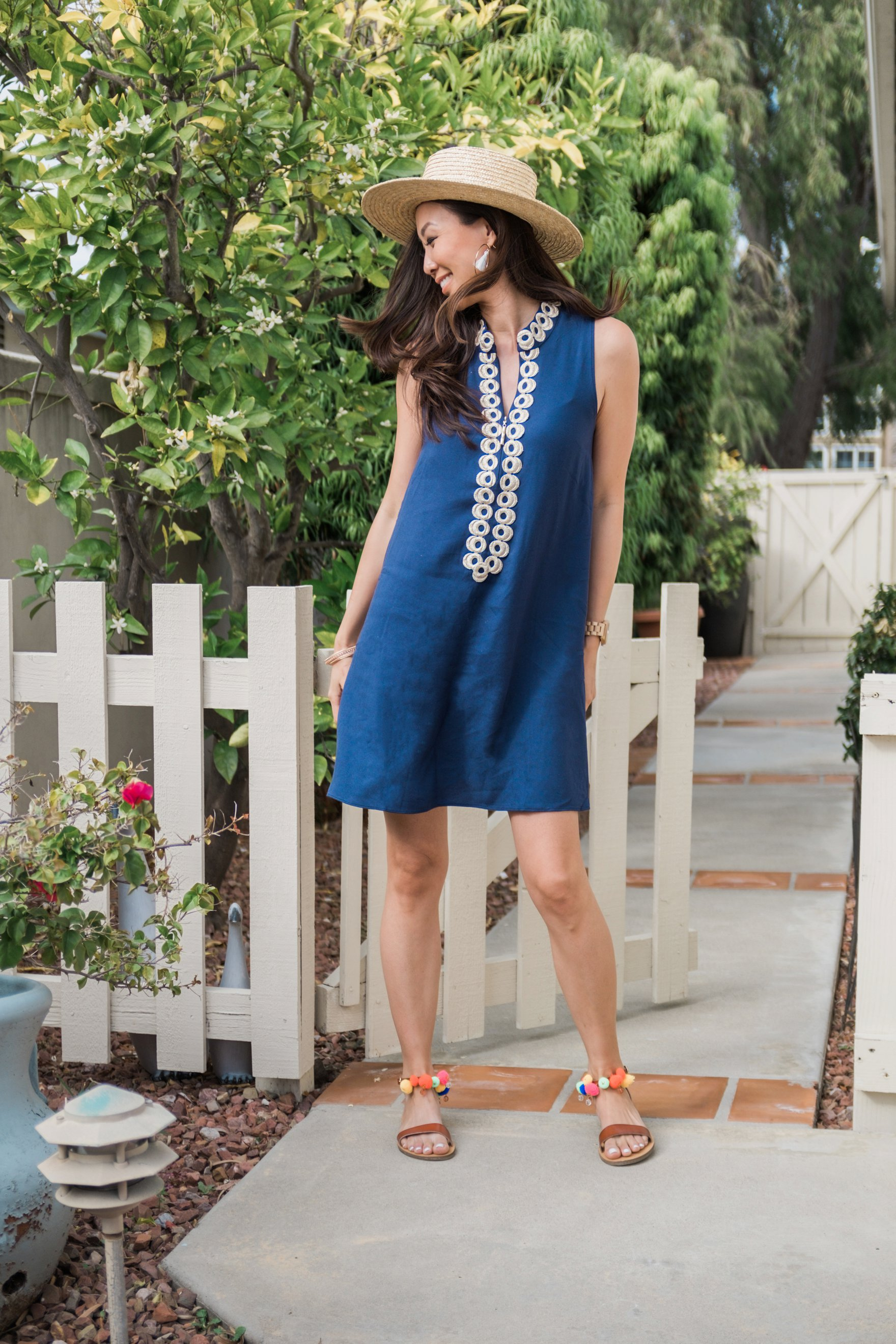 navy Lilly pulitzer Jane shift dress with sunhat on blogger Diana Elizabeth in San Diego leaning against white picket fence