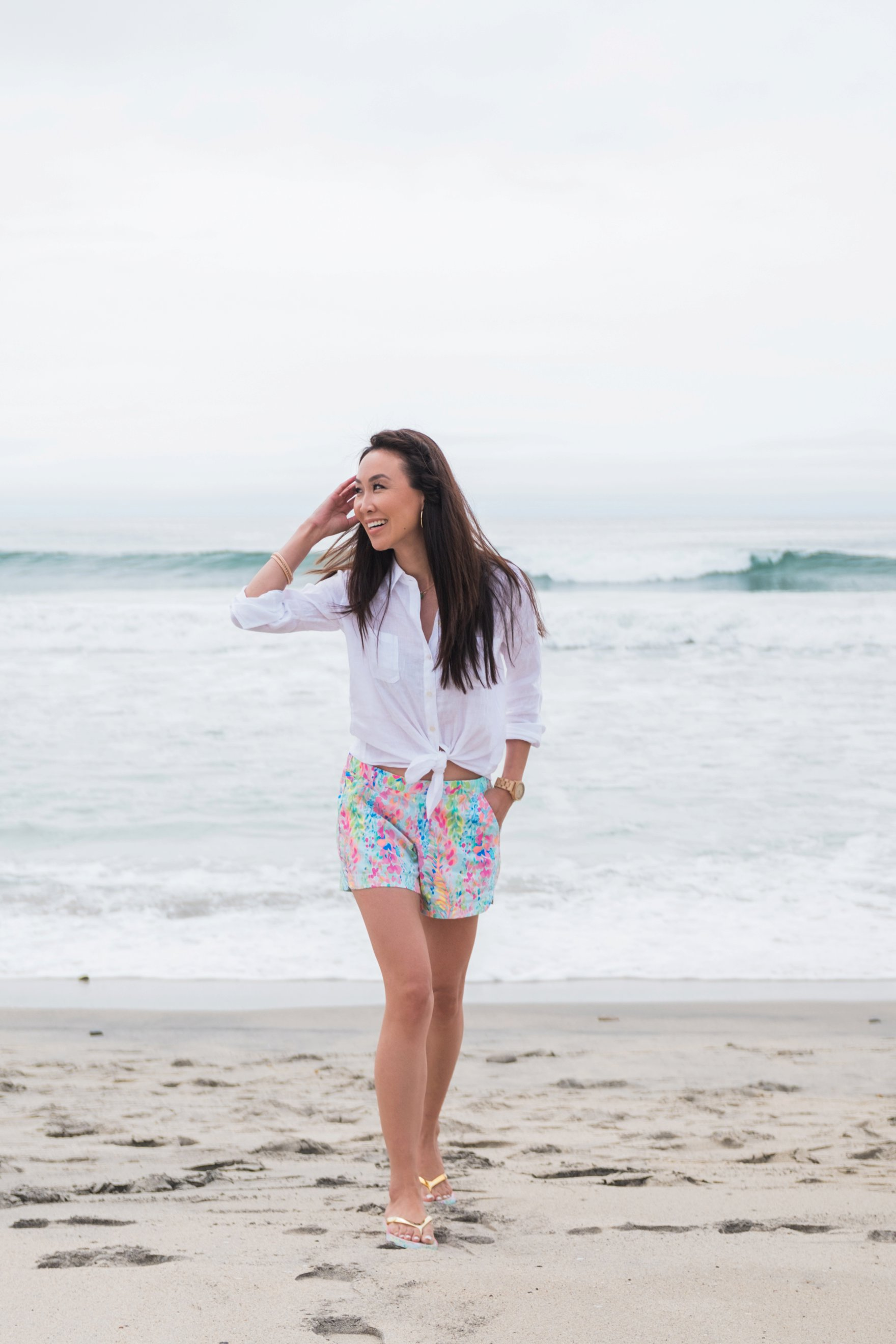 Carlsbad state beach wearing Lilly Pulitzer ocean view boardshort Diana Elizabeth blogger walking on beach wearing linen button up shirt