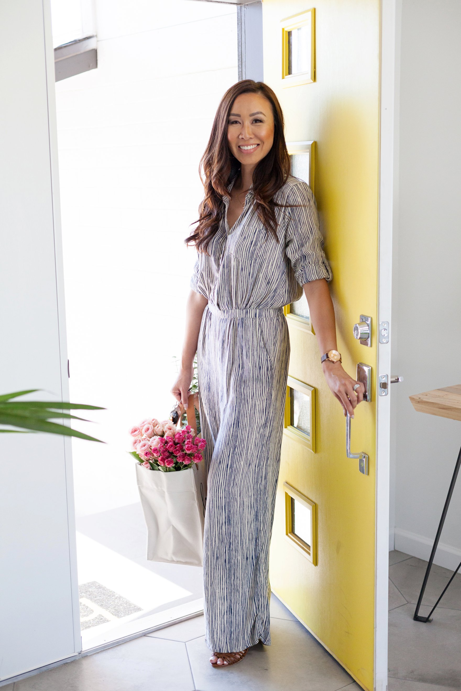 yellow front door Diana Elizabeth blogger holding florals walking in