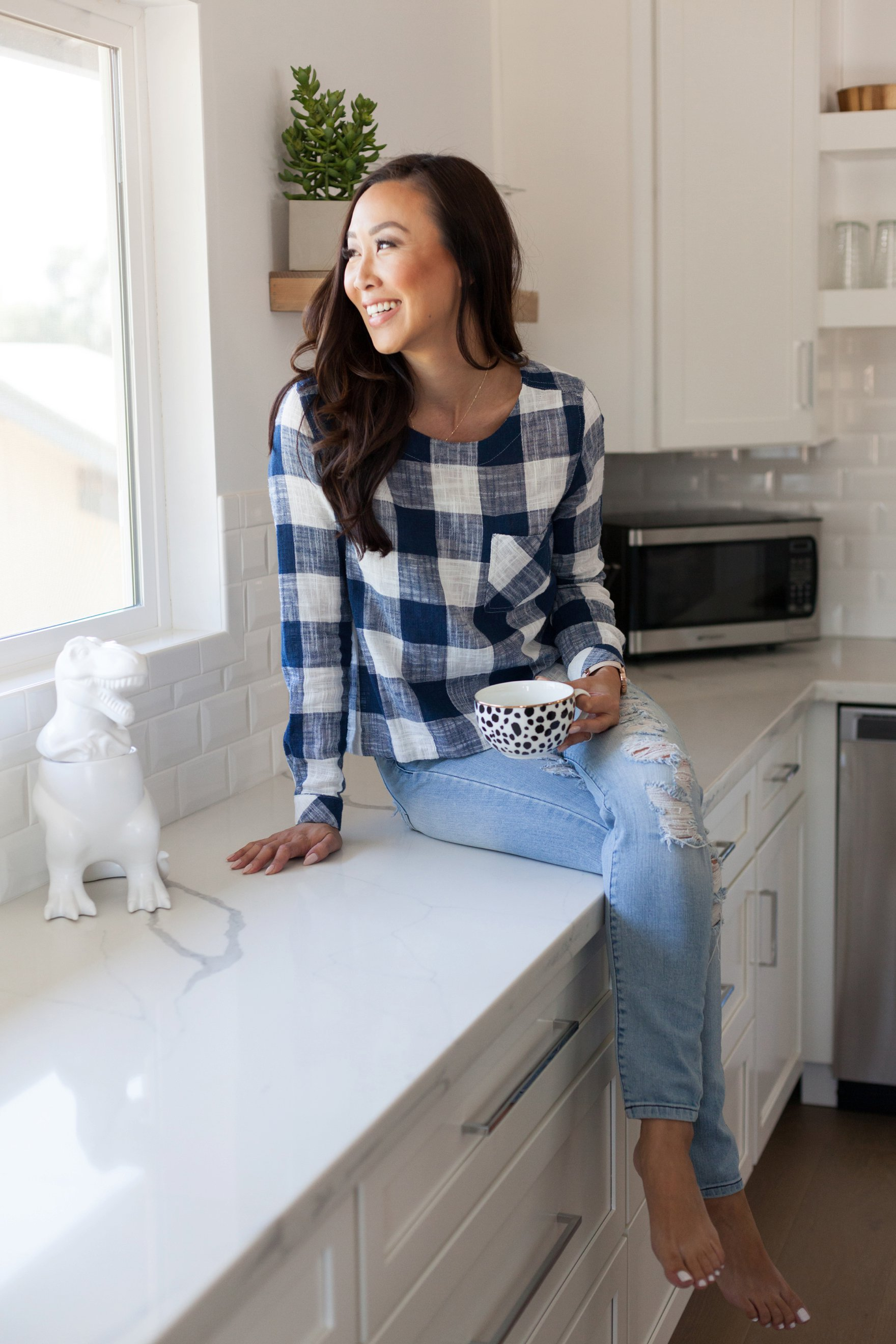 Diana Elizabeth in blue white gingham top on kitchen counter