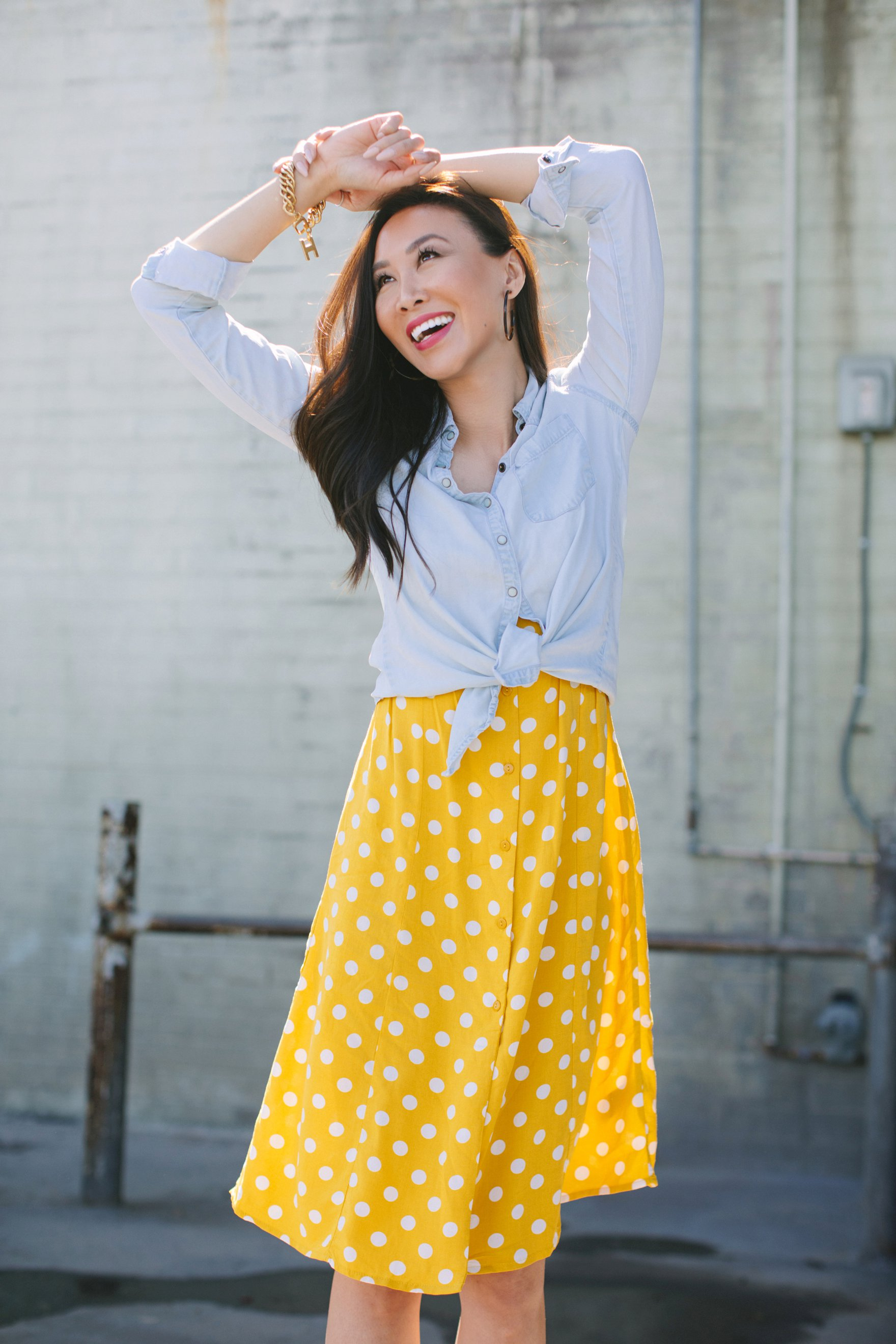 Yellow and white polka dot dress forever 21 paired with a chambray top featuring India hicks bracelet and other jewels lifestyle blogger Diana Elizabeth with hand over head pose