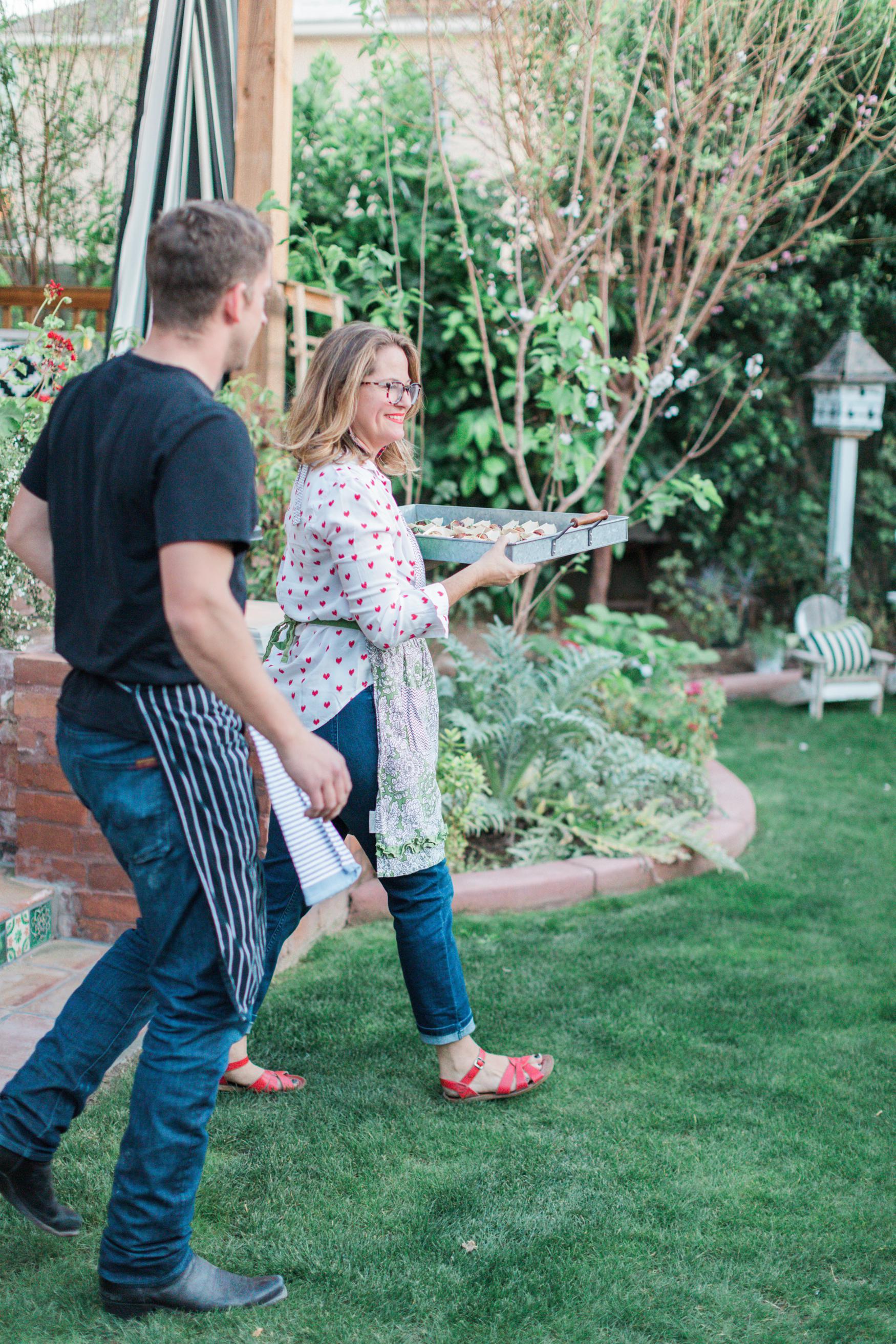 Boho Farm and Home Dinner theme Spain in backyard tapas. Caroline serving first entree.